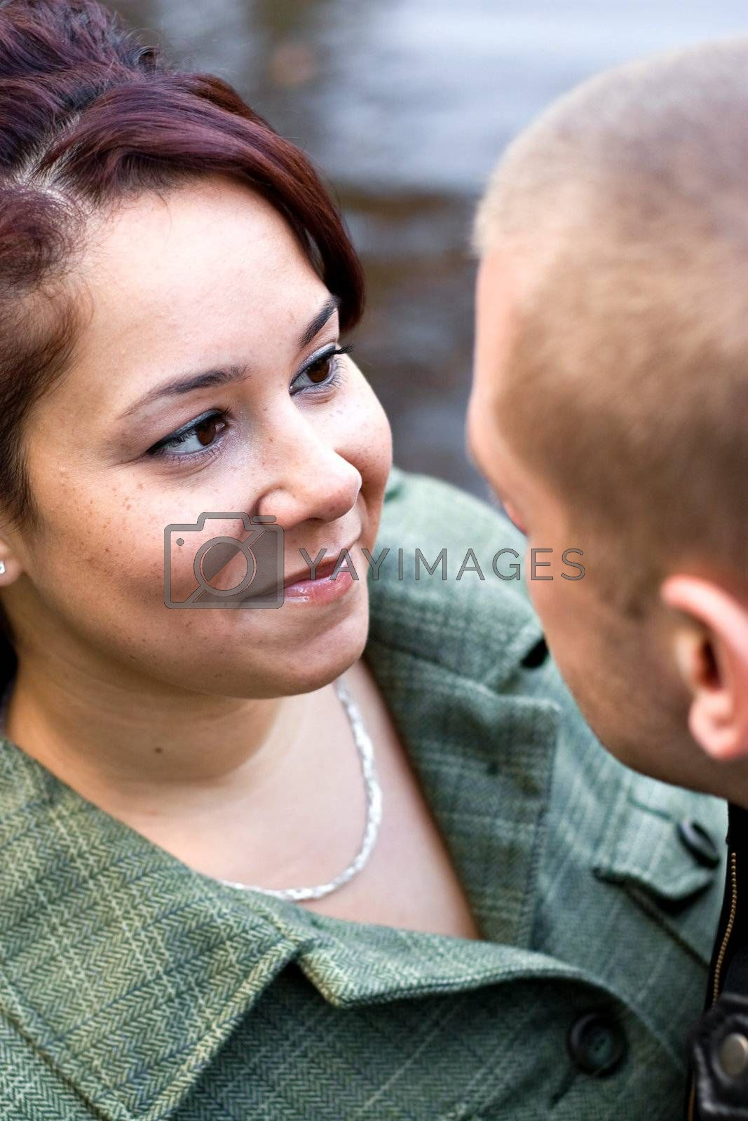 A young happy couple looking at one another outdoors. Shallow depth of field with focus on the woman.