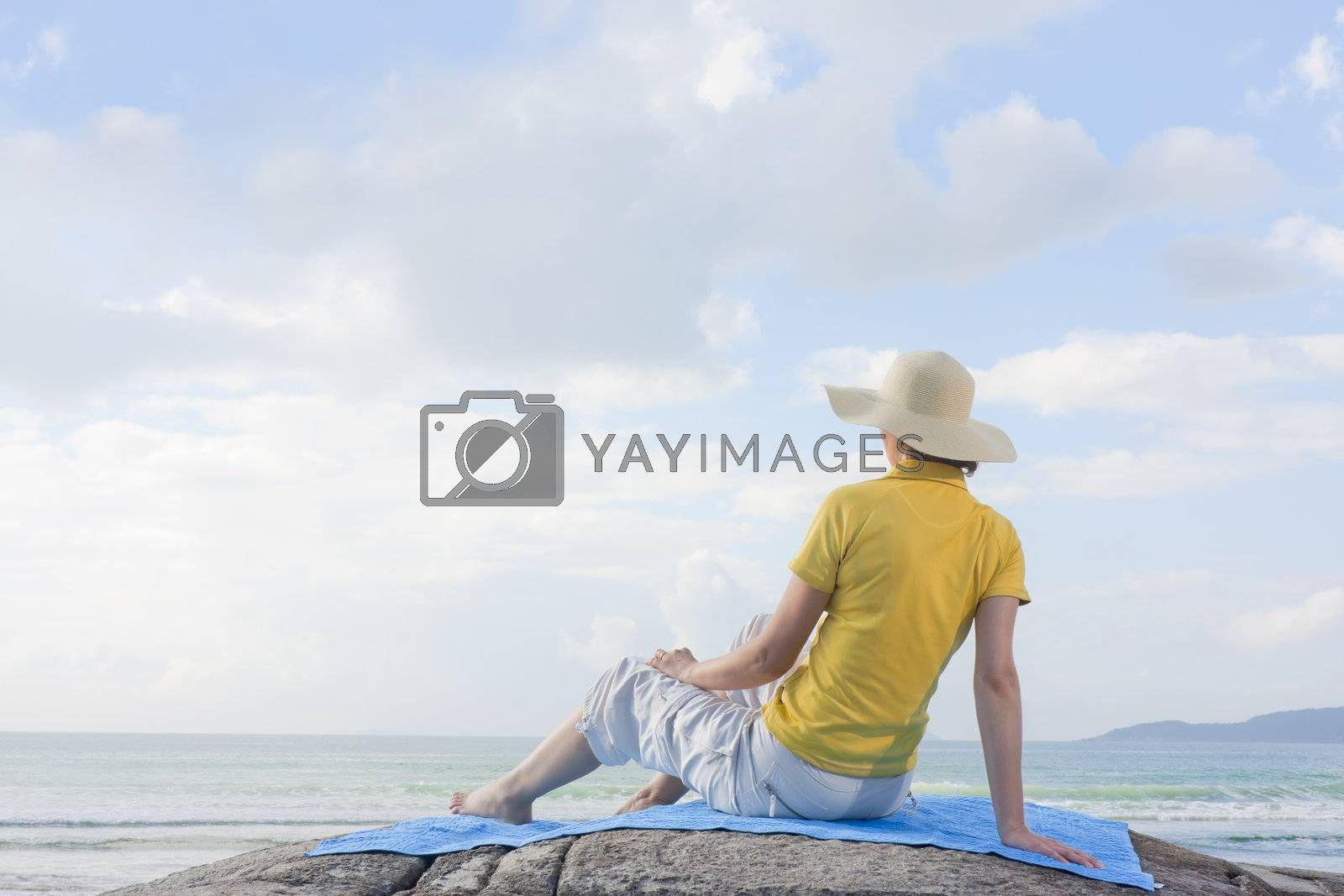 Mid-adult woman with straw hat sitting on a rock looking at the sea