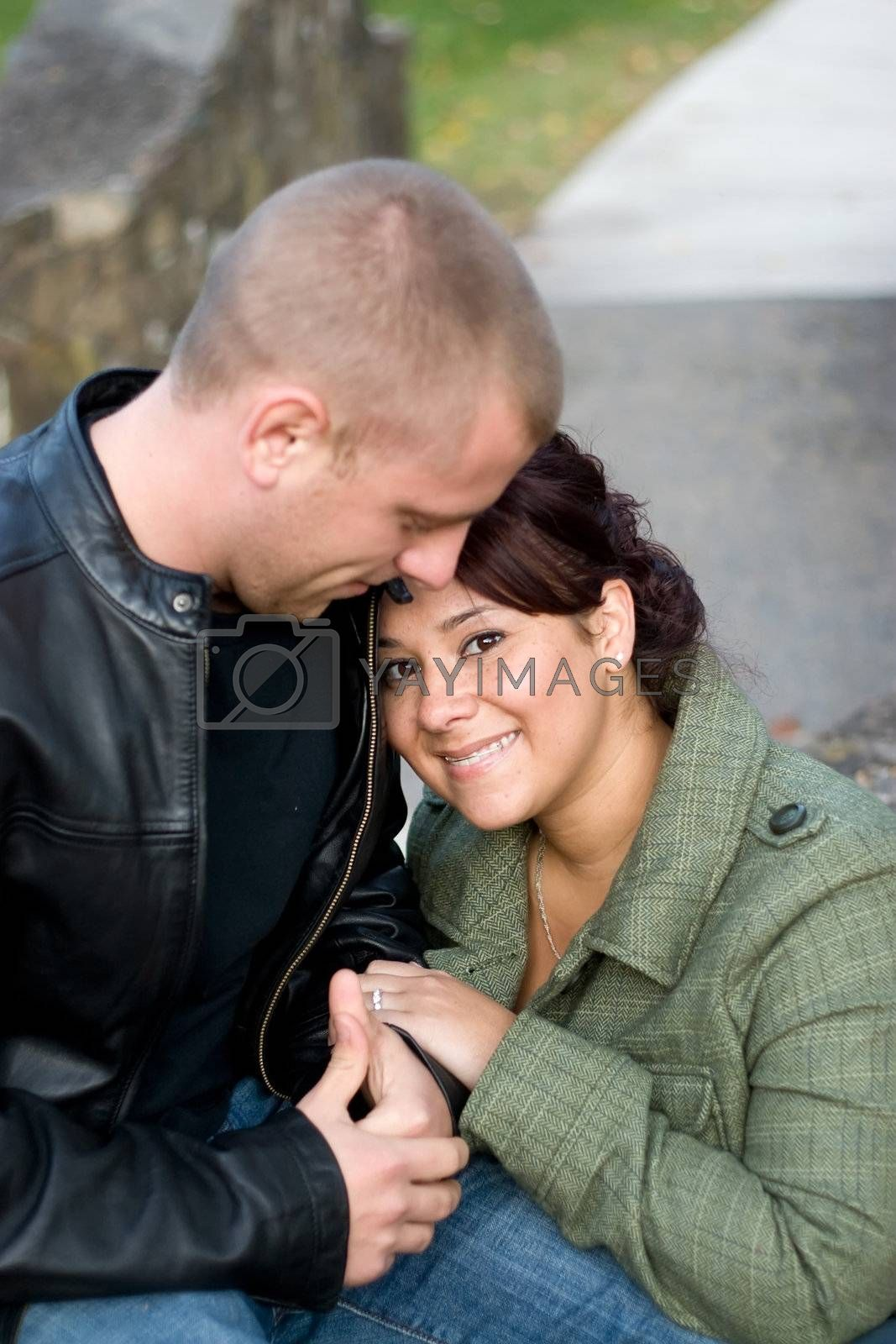 A happy interracial couple cuddling together outdoors. Shallow depth of field.