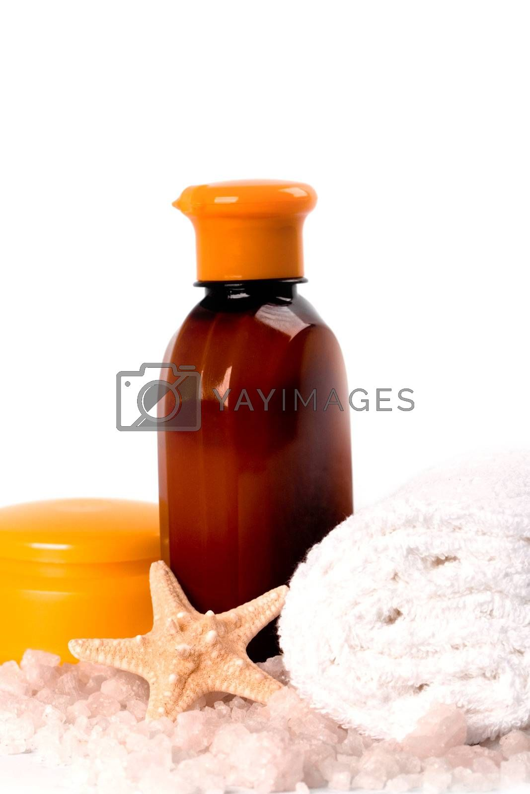spa products: sea salt, creme, towel, body lotion and seastar closeup on white background