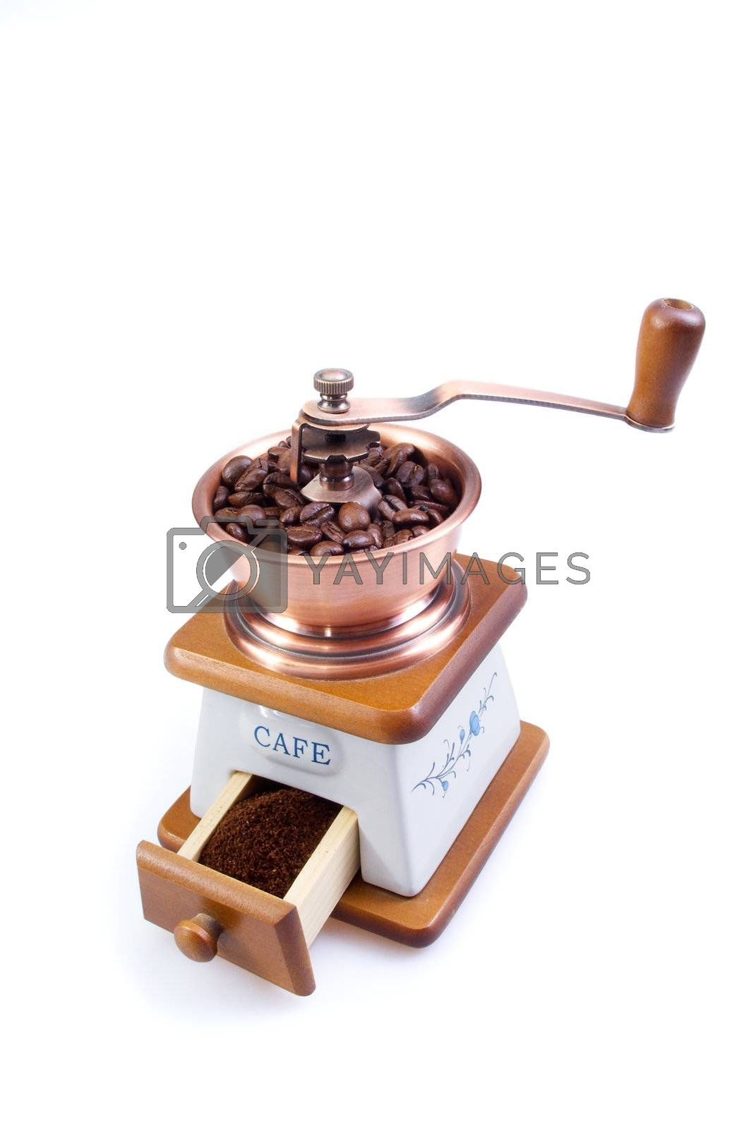 Royalty free image of The ancient coffee grinder with coffee grains by BIG_TAU