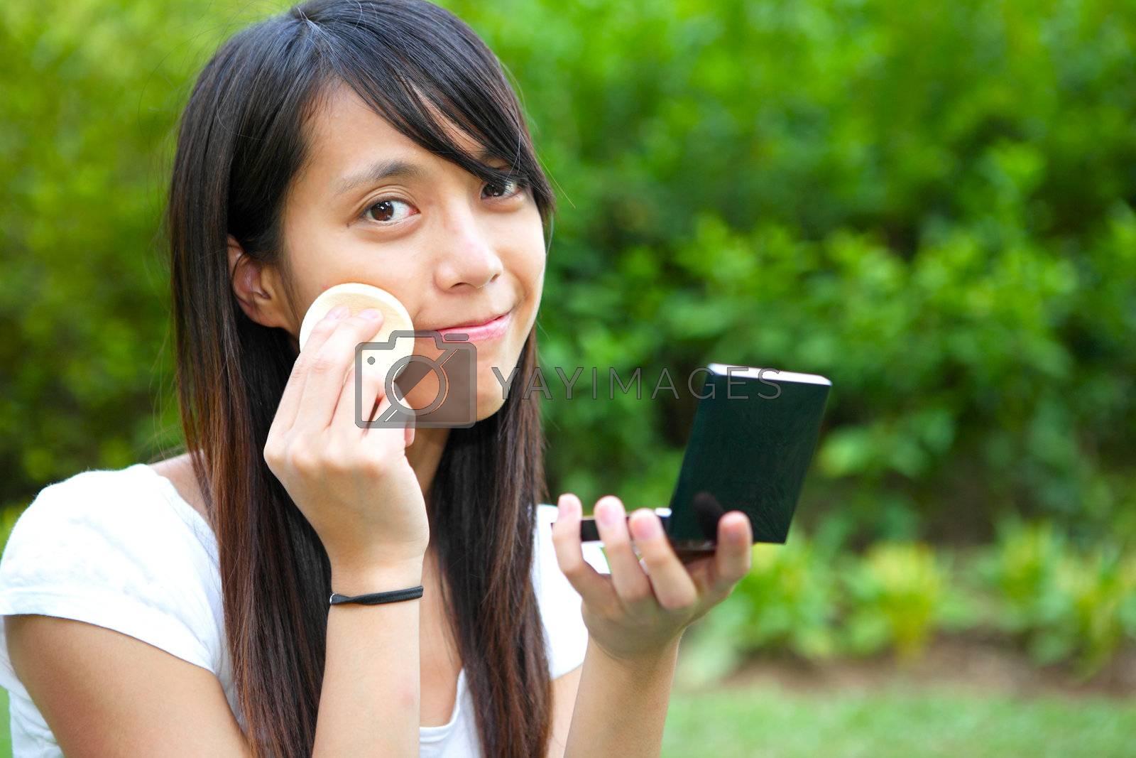 Royalty free image of woman doing makeup by leungchopan