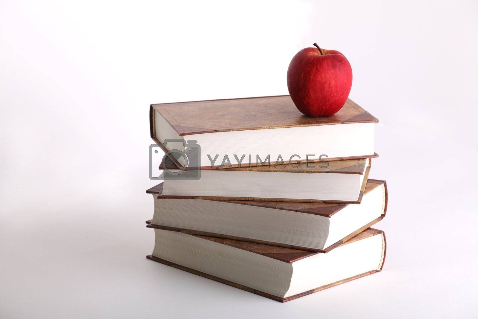 Red apple on the stack of the books on white background