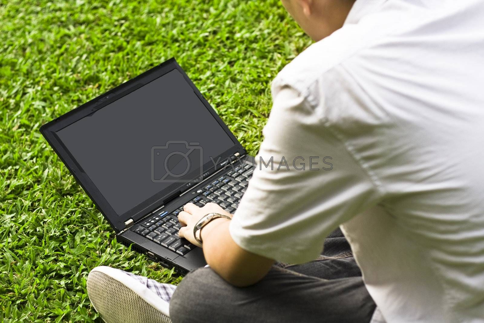Man siting on the grass using laptop for texture