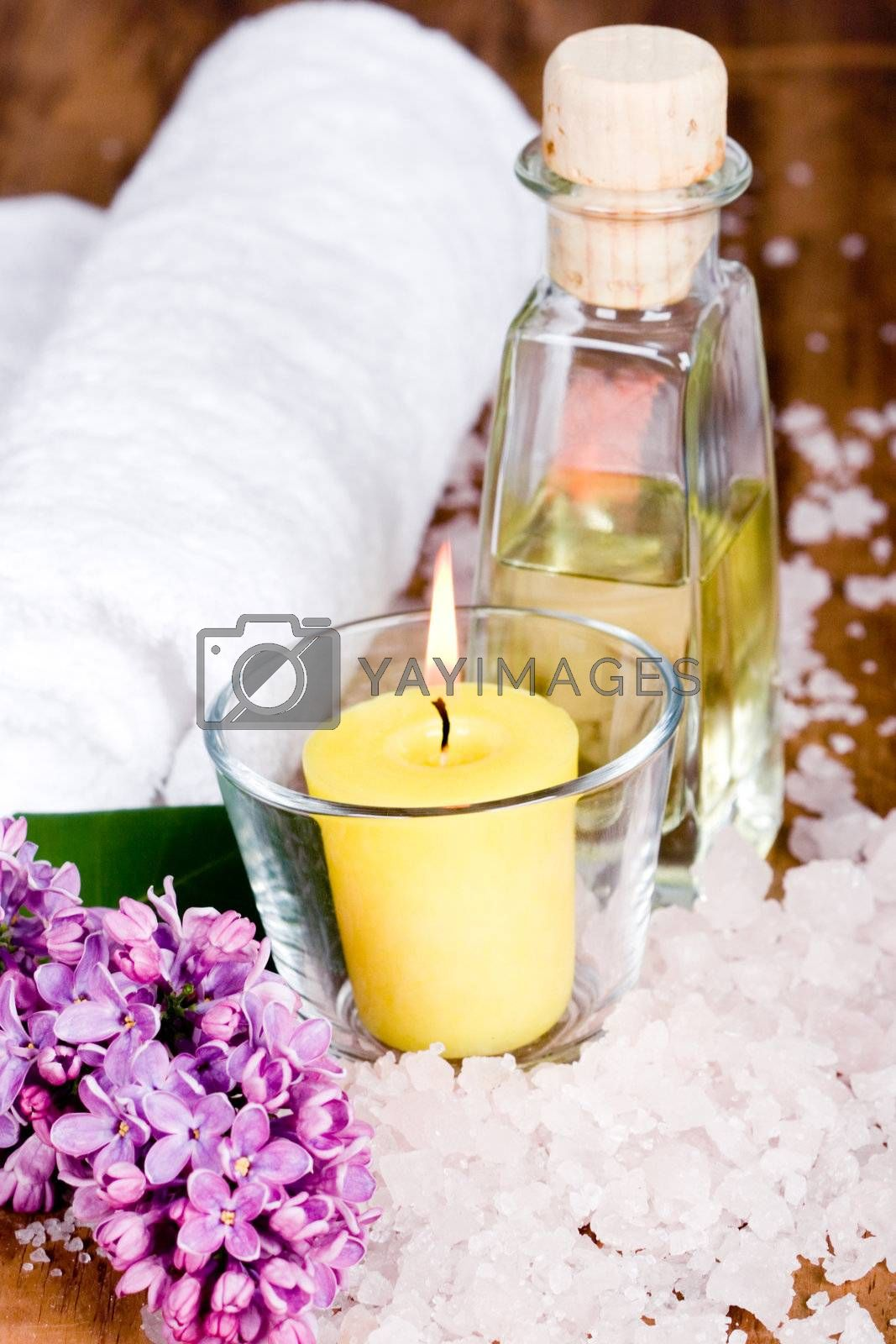 bath and spa items (towel, salt, oil, lilac, candle) on wooden background
