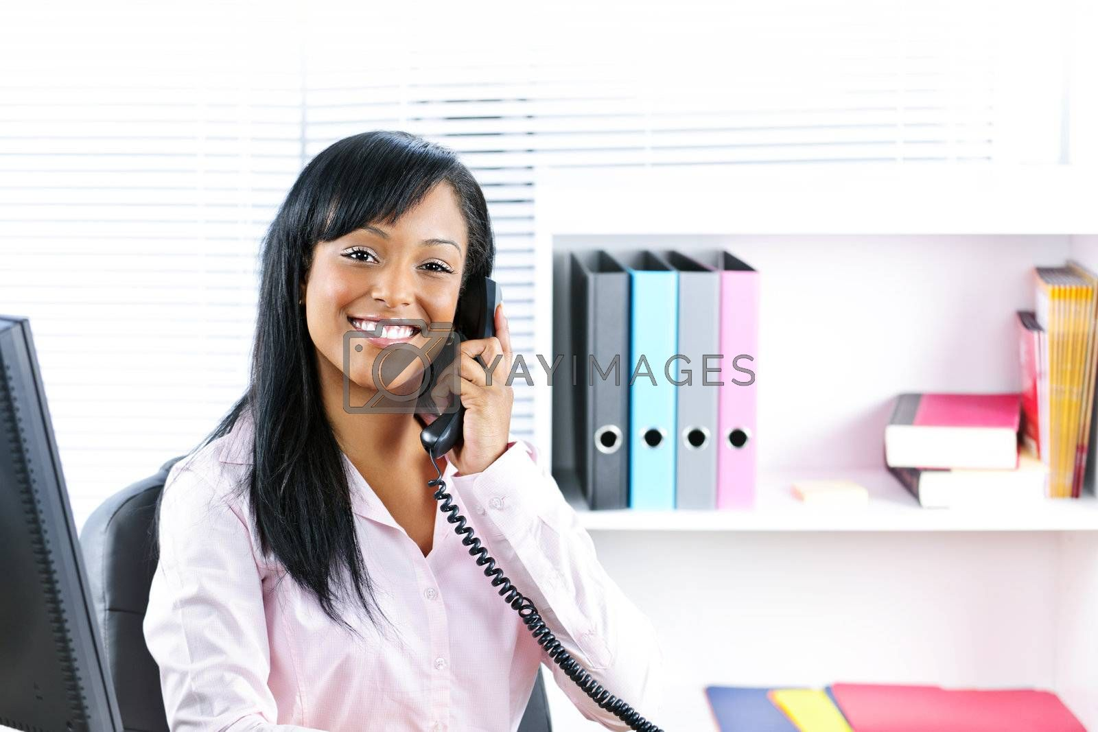 Smiling black businesswoman on phone at desk by elenathewise