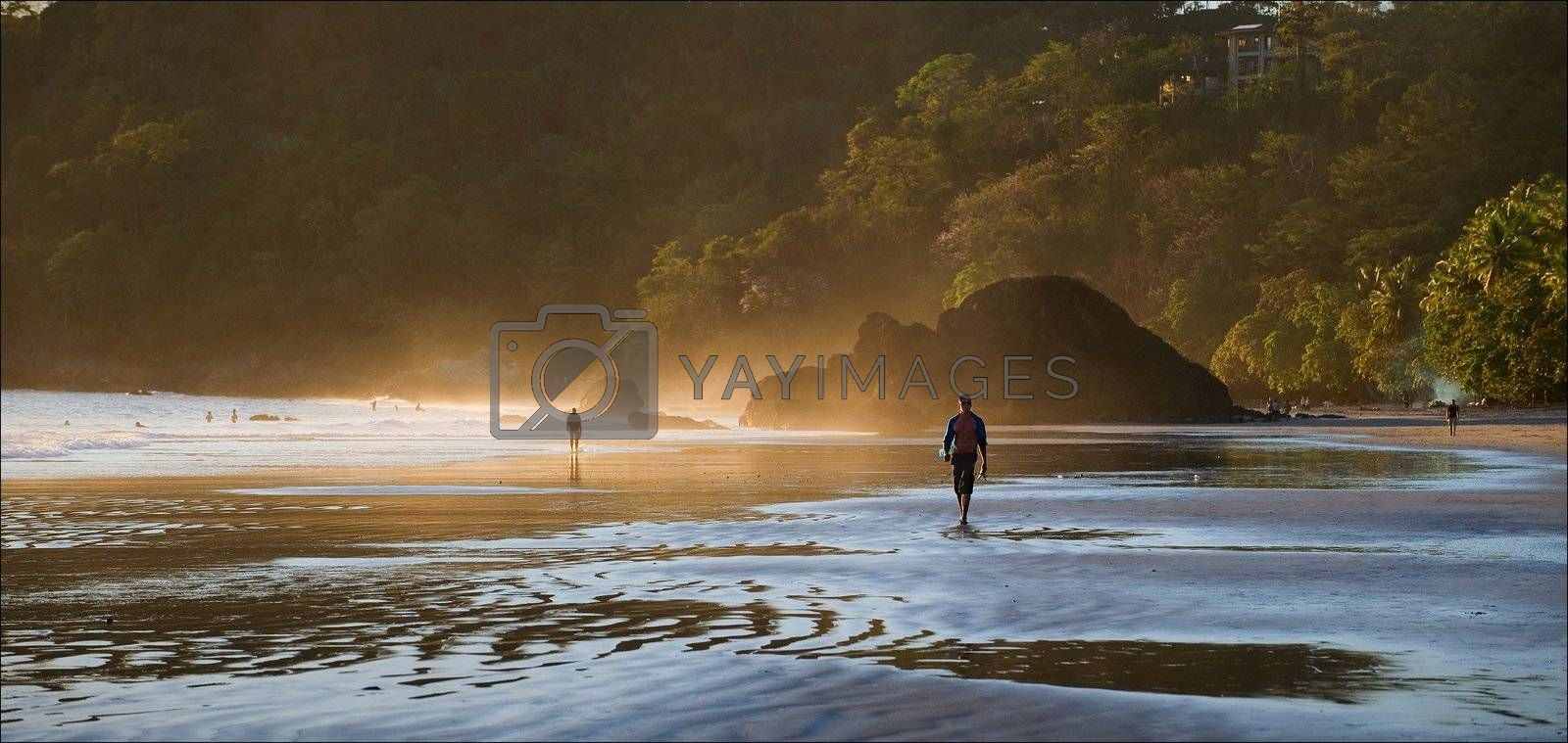 Dawn at coast of Pacific ocean. Wet sand, foggy a smoke and the walking person.