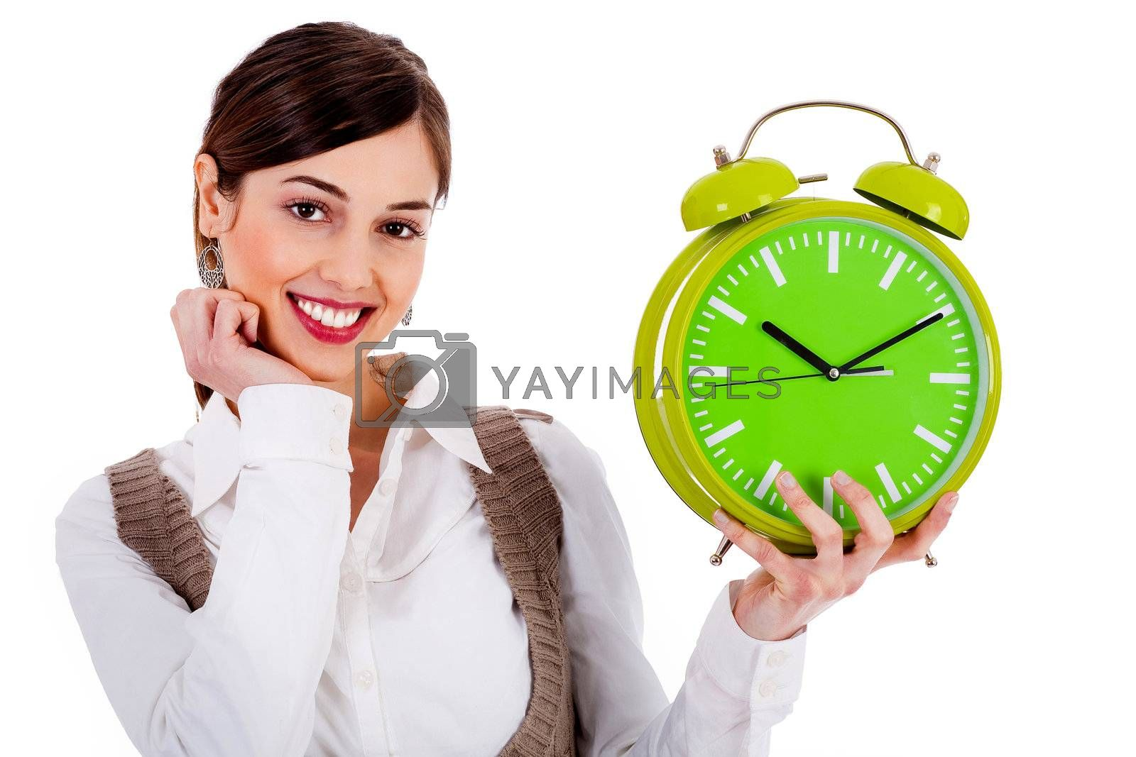 Portrait of lady holding alarm clock with one hand and one hand on chin against white background