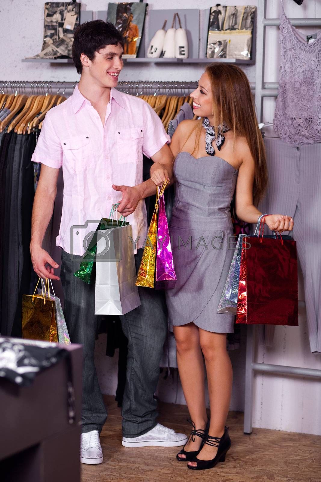 Young modern couple carrying shopping bags and looking at each other
