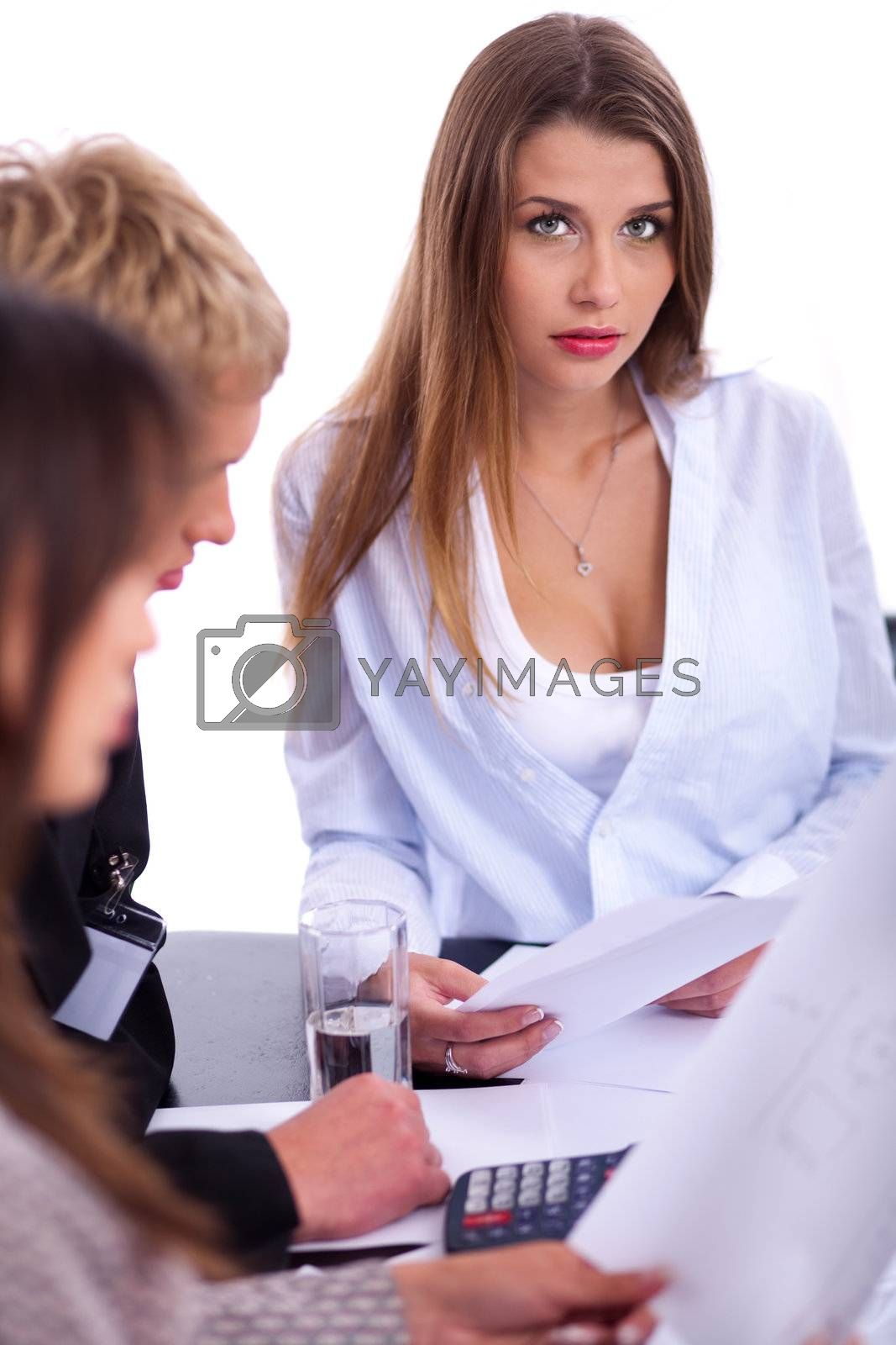 Businesswoman looking at camera while attending business meeting with her colleagues