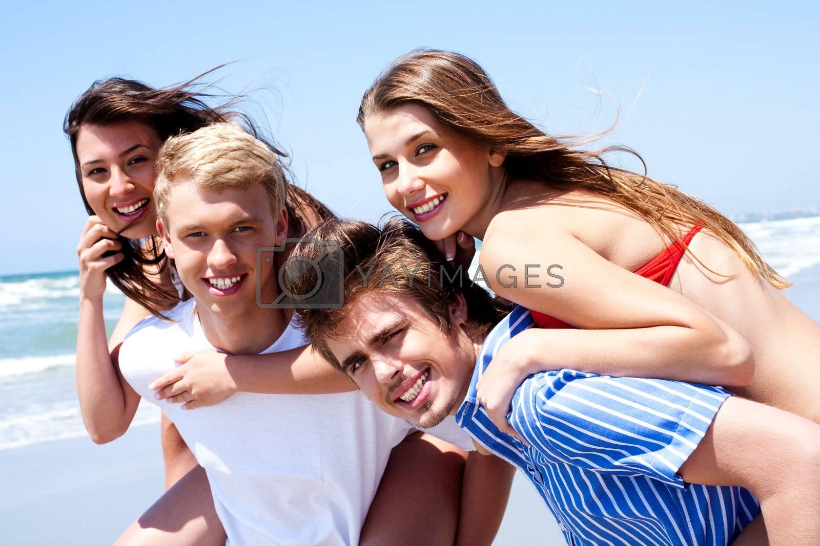 Young women enjoying piggyback ride by the beach
