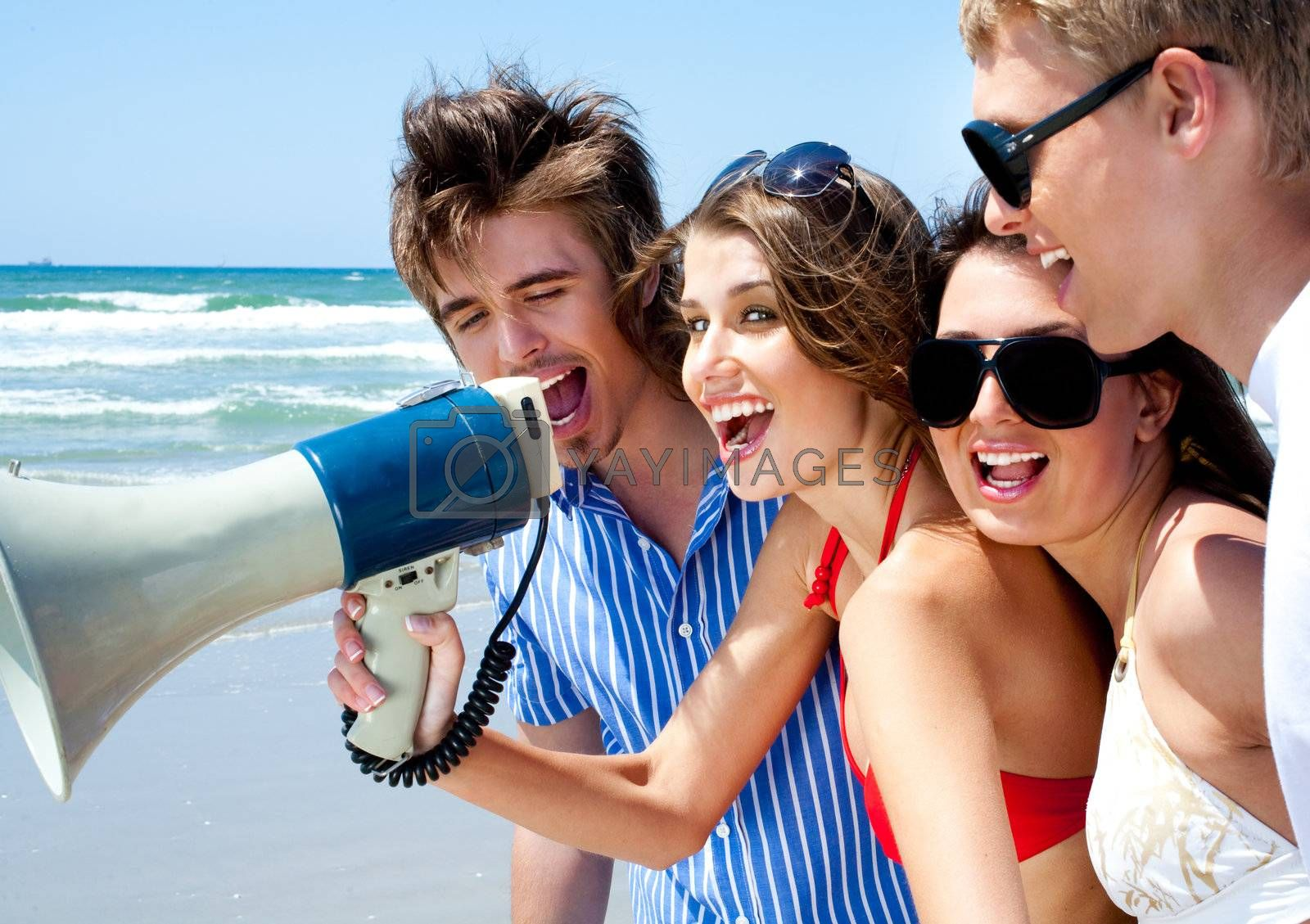 Happy young couples shouting through megaphone  on the beach in the summer