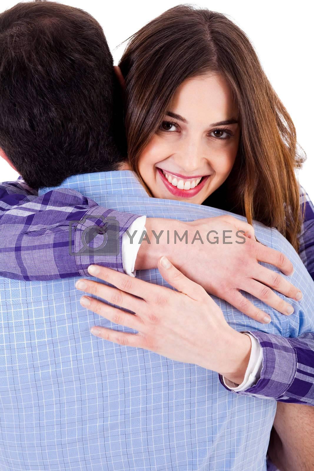 closeup of smiling young woman hugging man and looking at camera