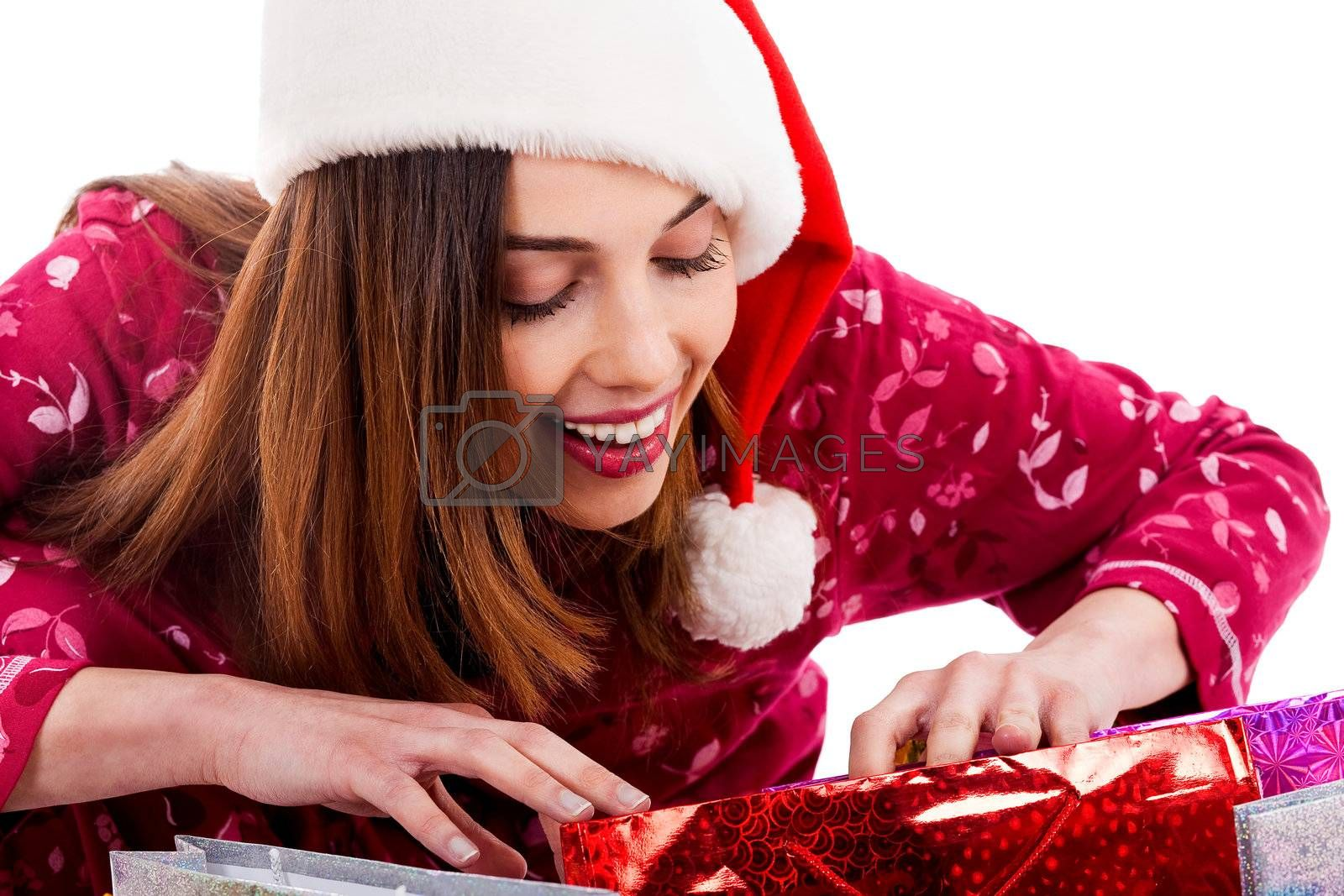 closeup of young lady wearing christmas hat peeping into christmas gift bags