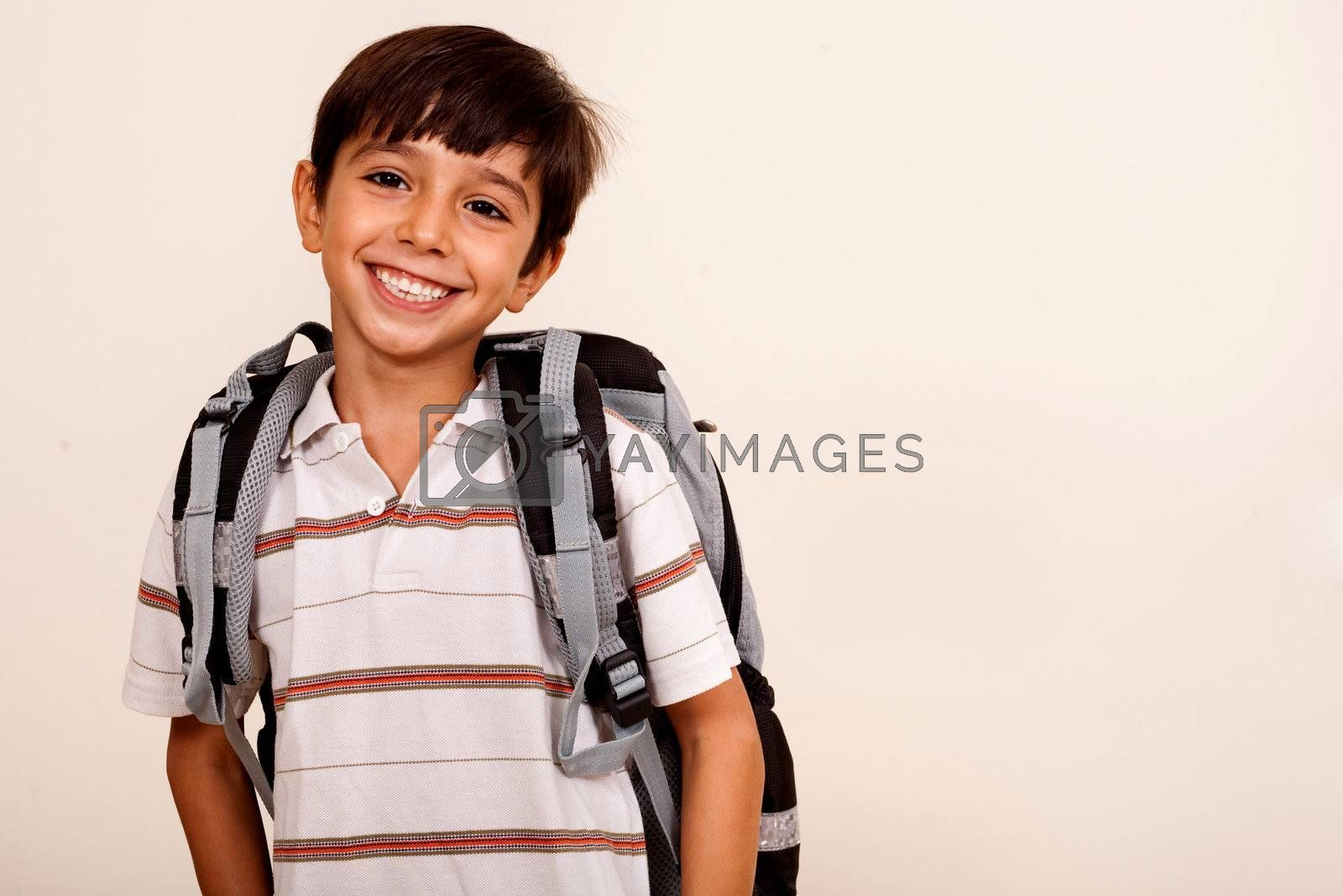 Portrait of smiling schoolboy with back pack isolated on ivory background