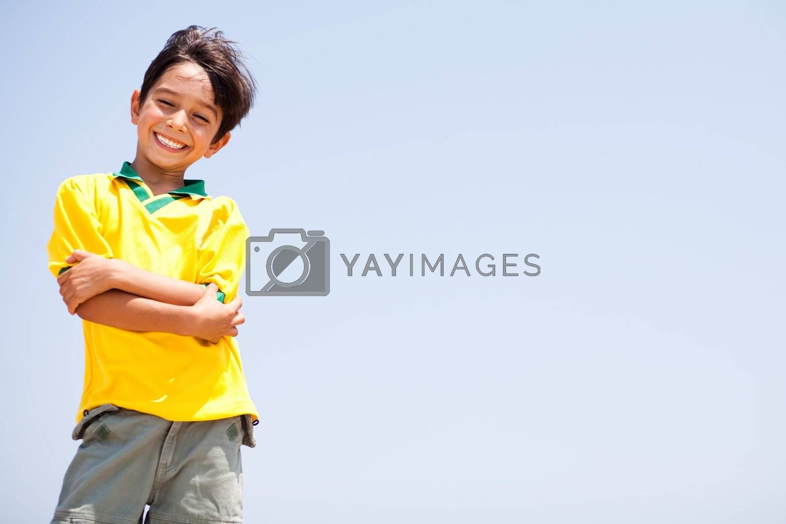 Charming kid posing with folded arms, smiling at camera