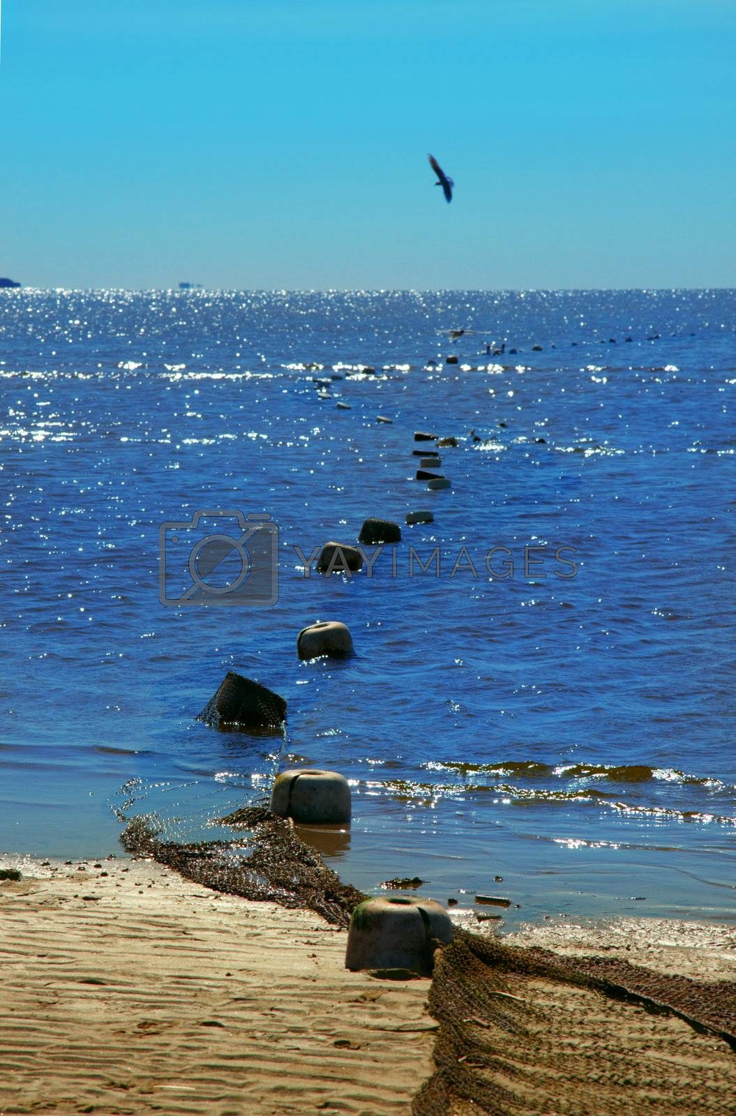Sandy coast of the dark blue sea under the blue sky. Fishing network with floats on sand and in the sea
