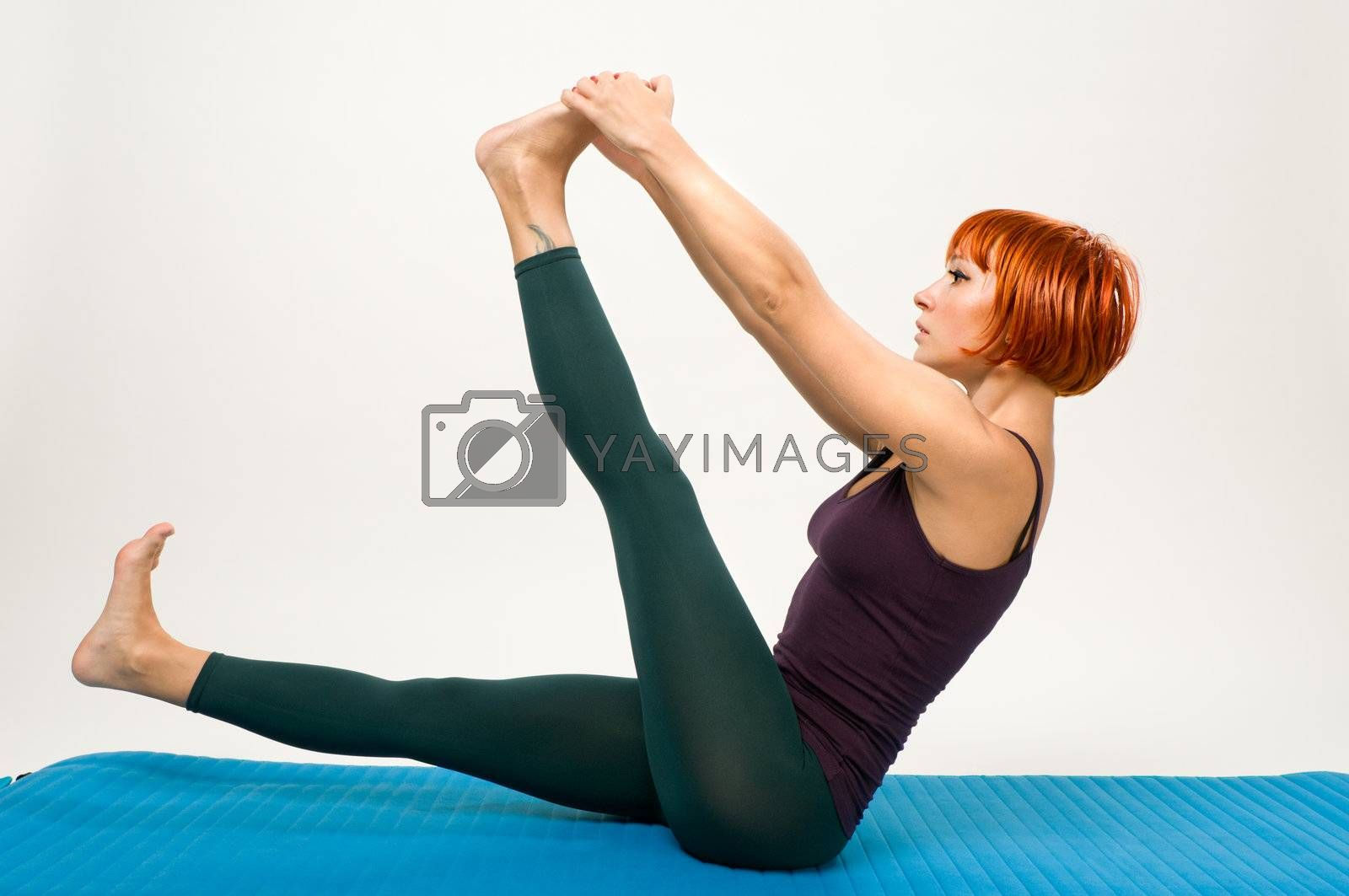 Beautiful red haired woman practicing fitness yoga in studio