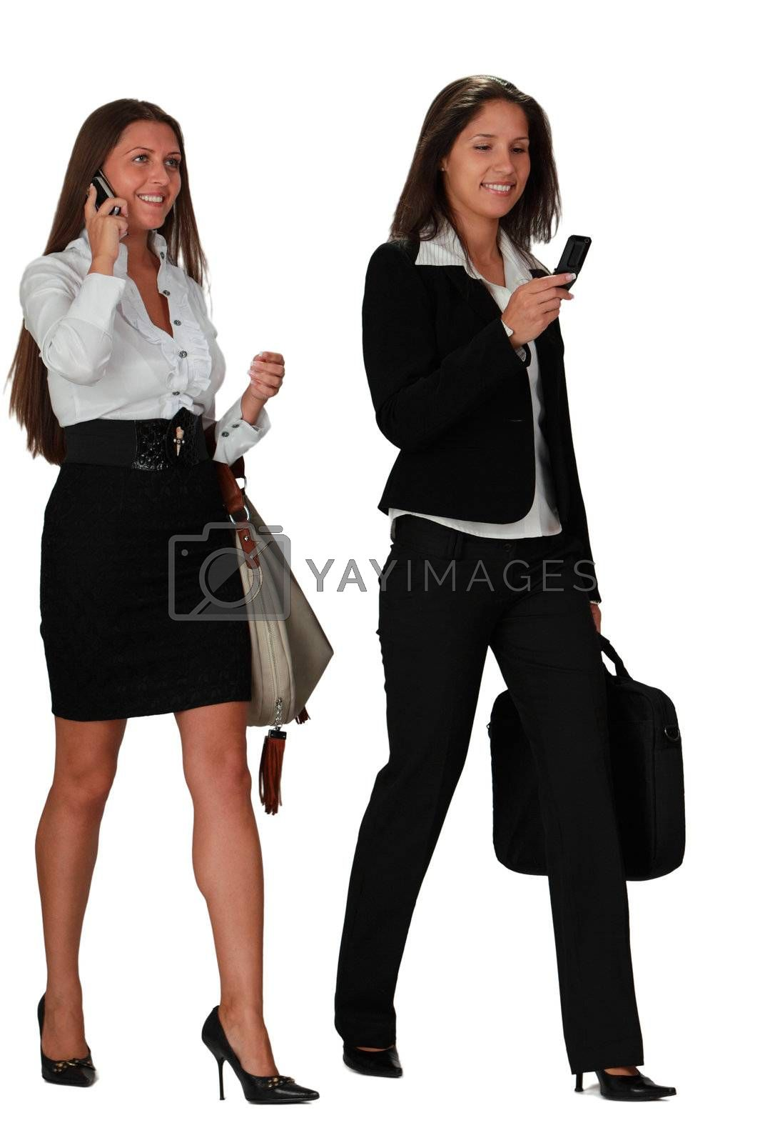 Two young women walking while using mobile phones,isolated against a white background.