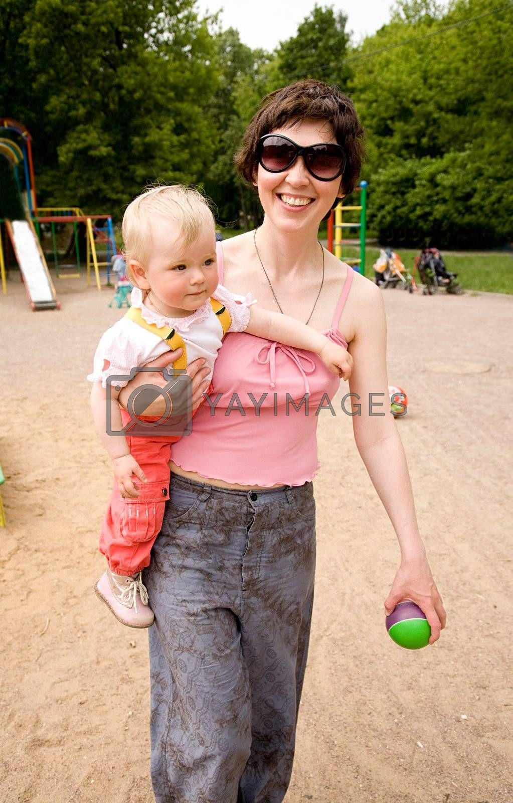 Beautiful harmonous mum with dark hair in sun glasses carries a little daughter and a green ball on a children's playground