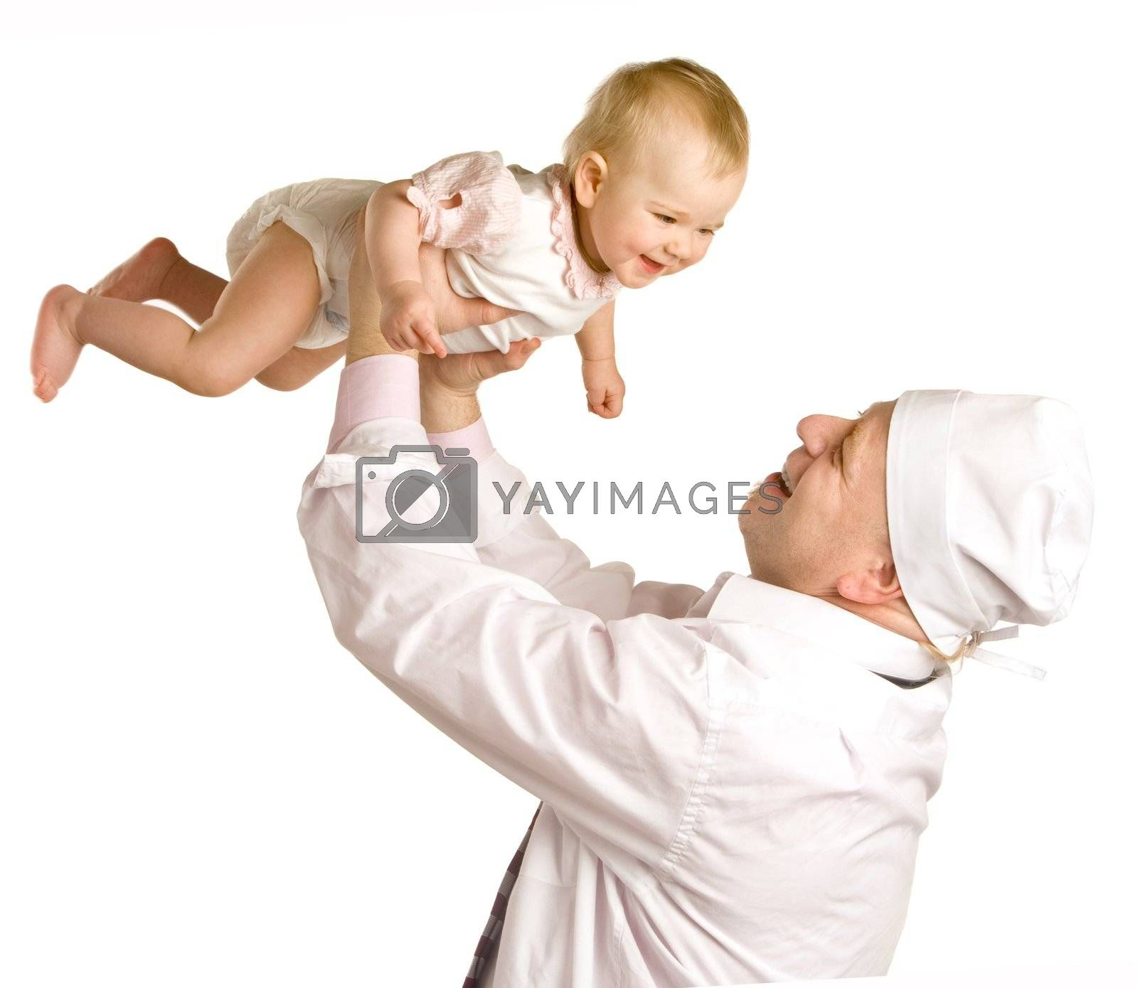The doctor in a white dressing gown holds on hands the small smiling girl in a dress on a white background