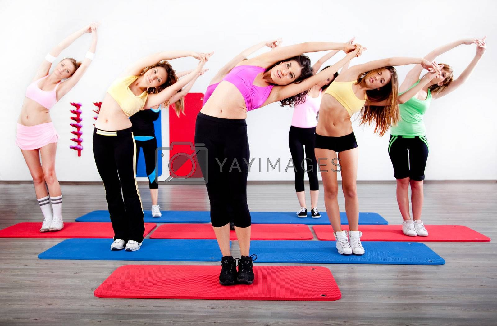 female stretching in an aerobics exercise class in gy