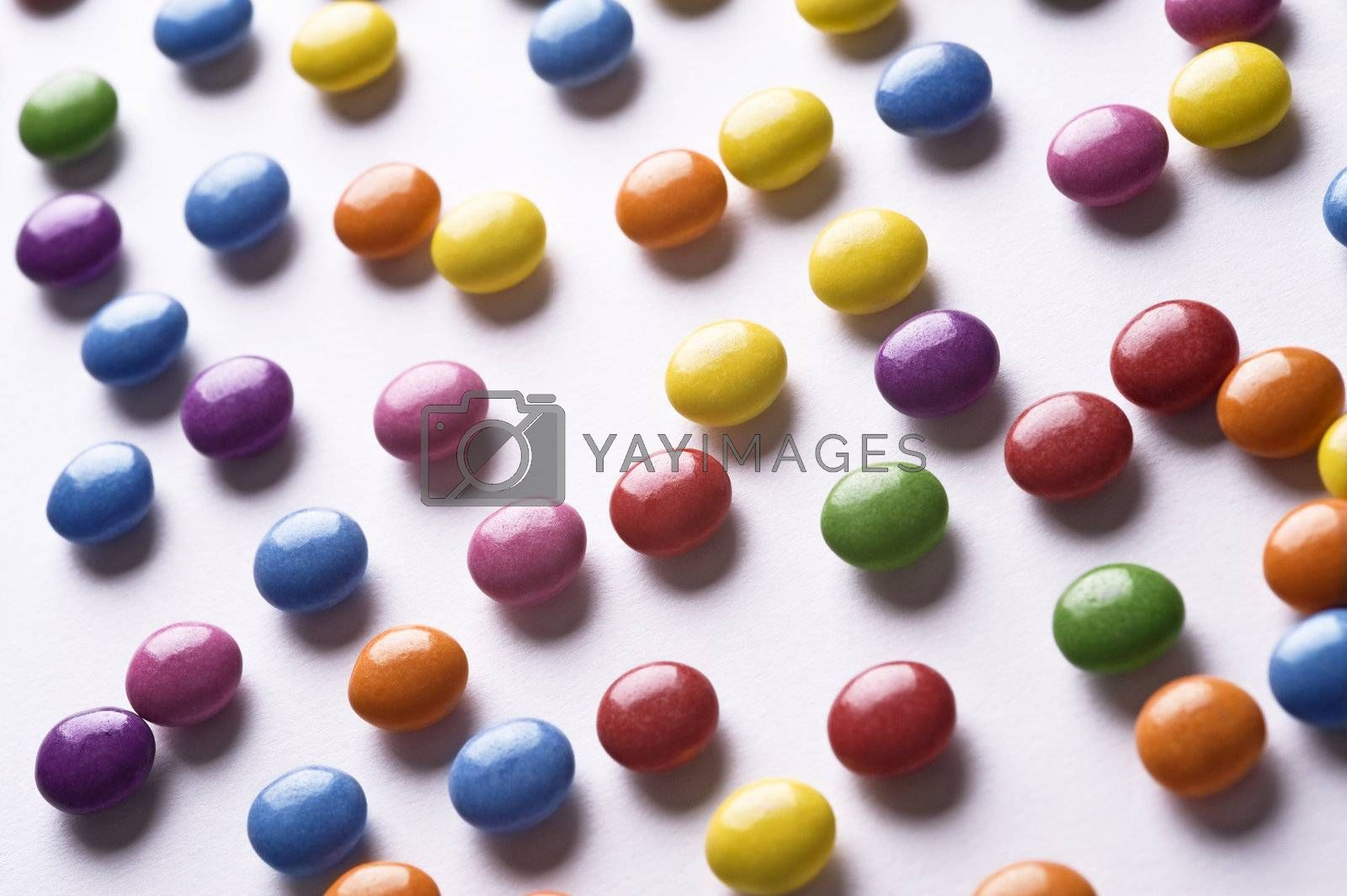 colorful pills scattered on white background