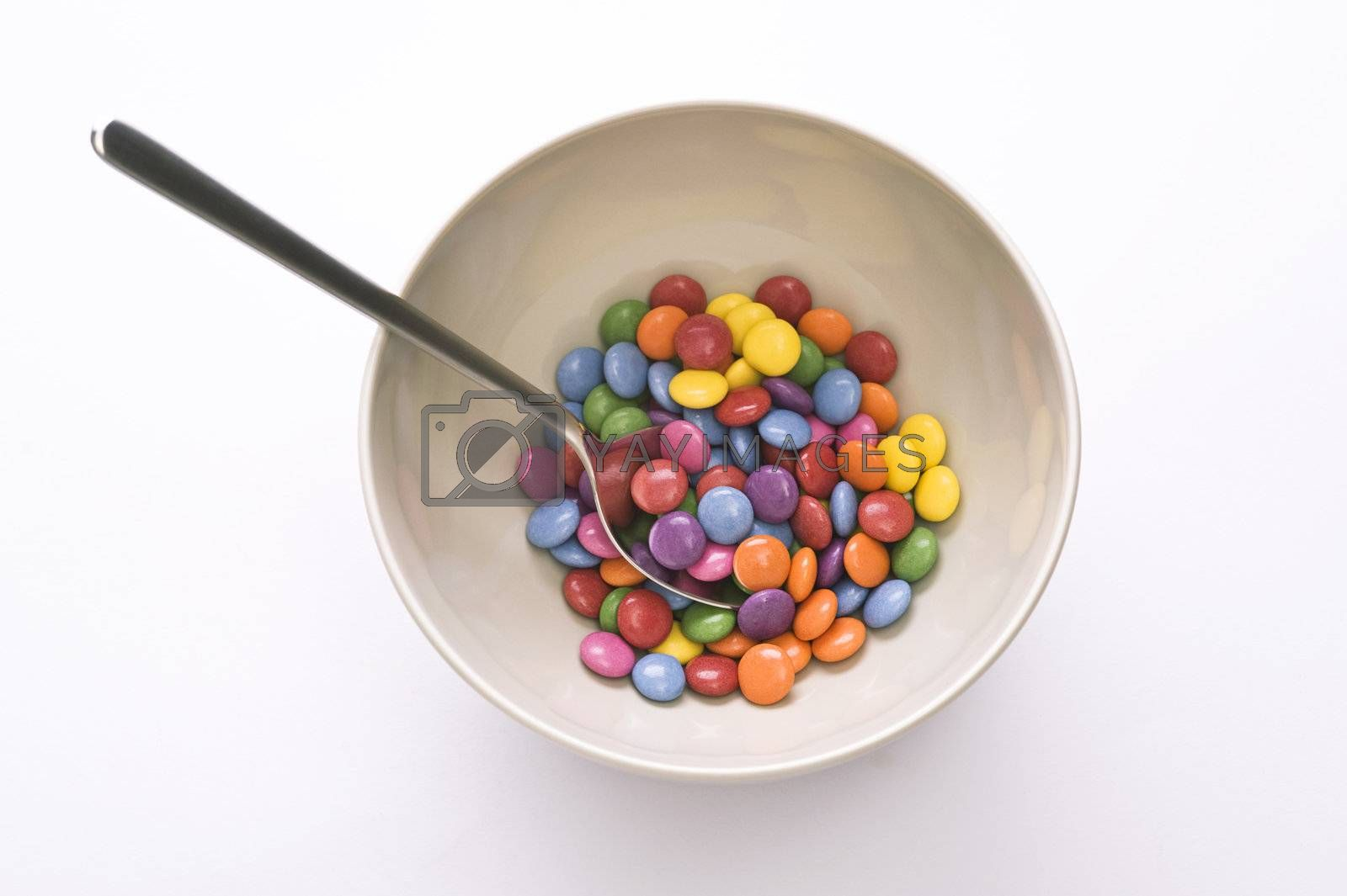 bowl with spoon and colorful sweets over white