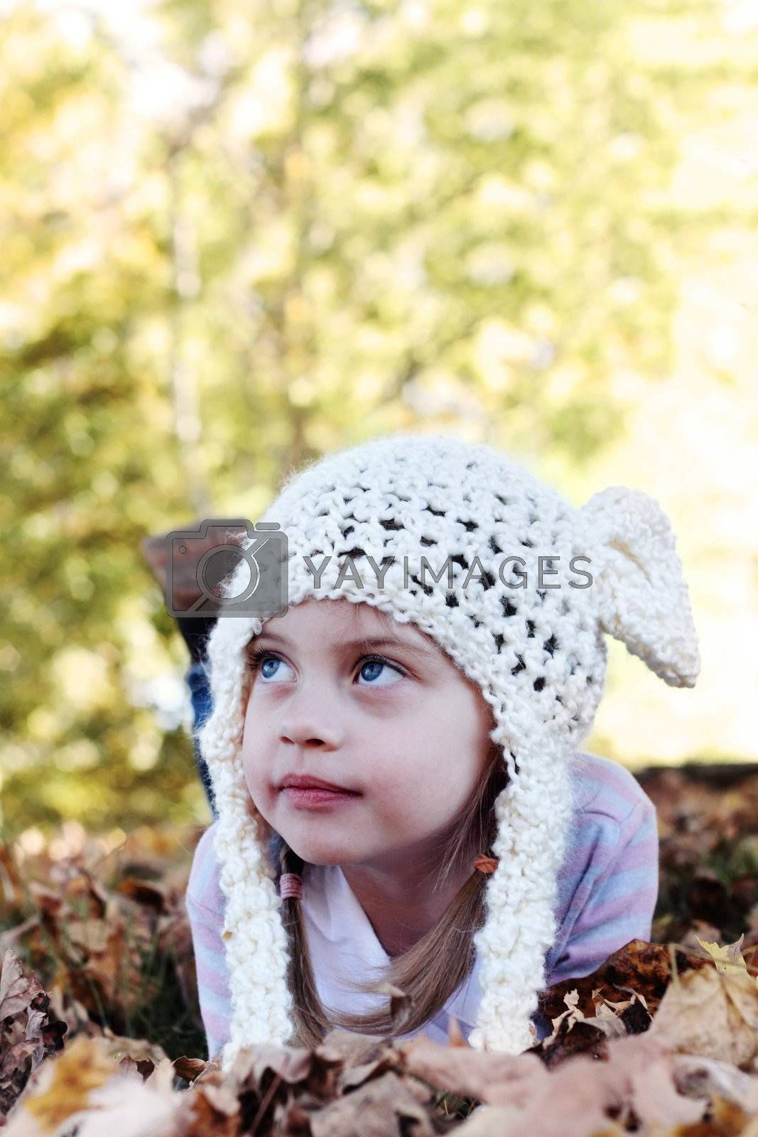 Beautiful little girl in a white bobble hat lying in the leaves and looking away from the camera. Selective focus on little girls face with shallow DOF.
