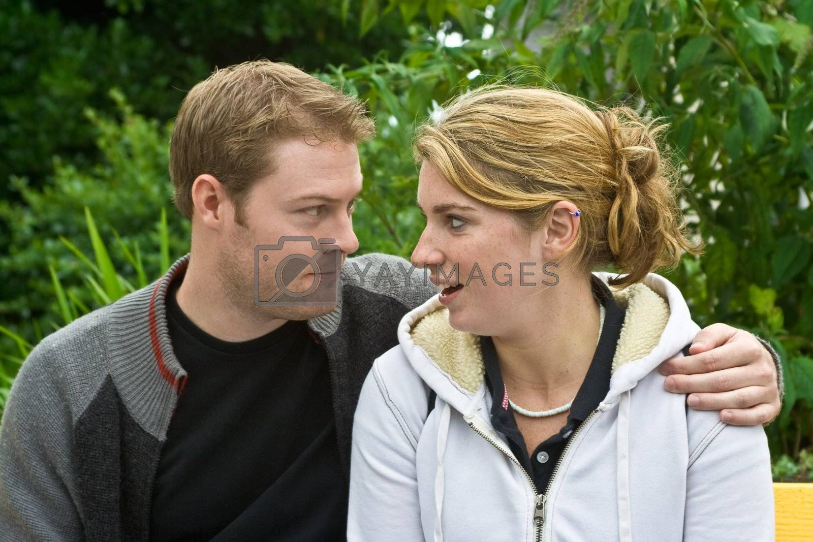A young man and woman on a bench. The young man has his arm around the woman and they are enjoying each others company.