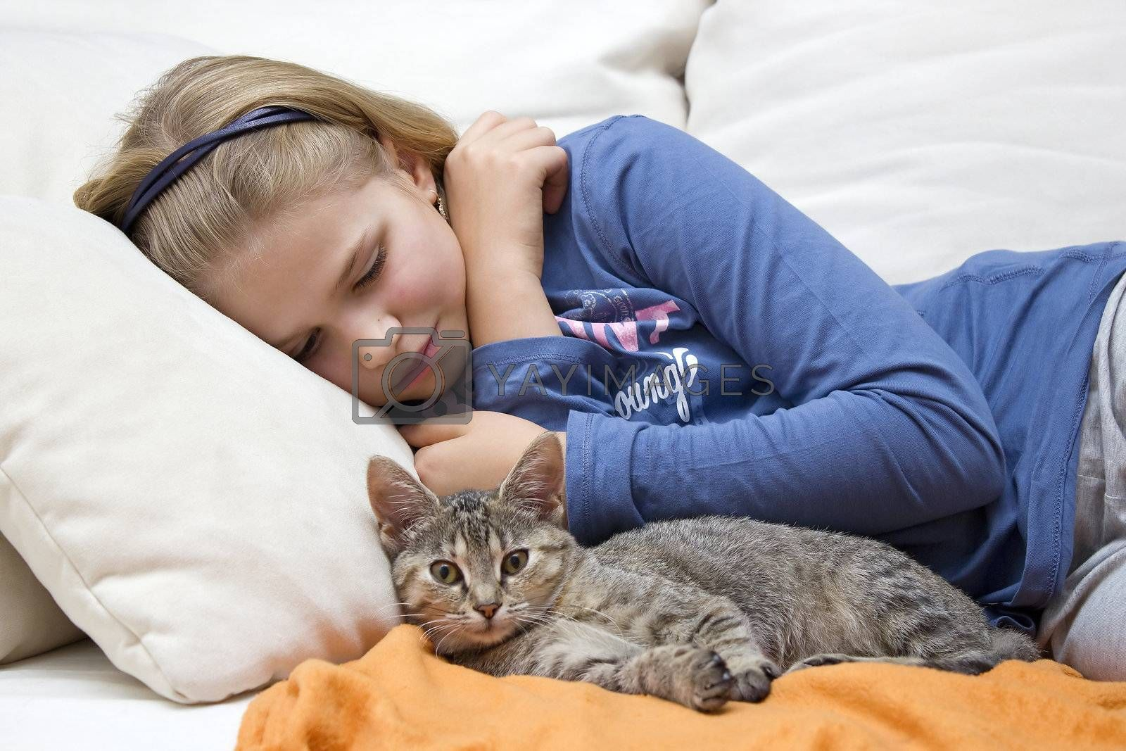 little girl and a kitten on the couch
