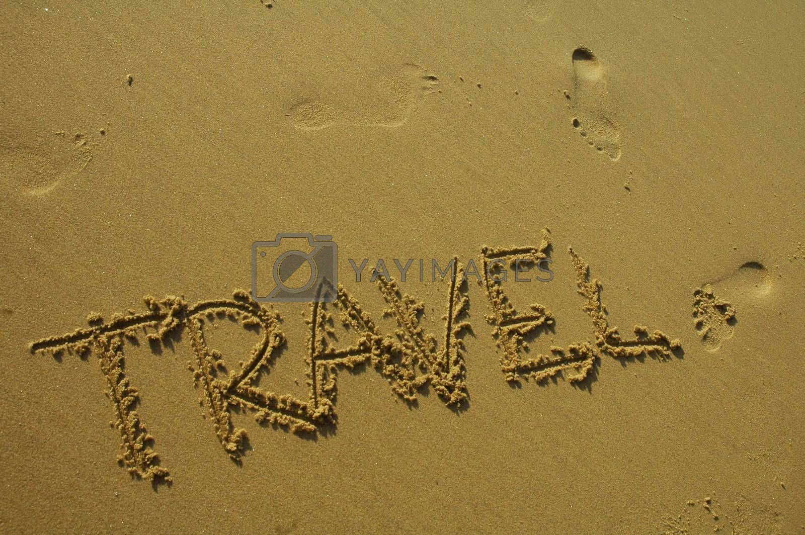 travel written in the sand on a beach