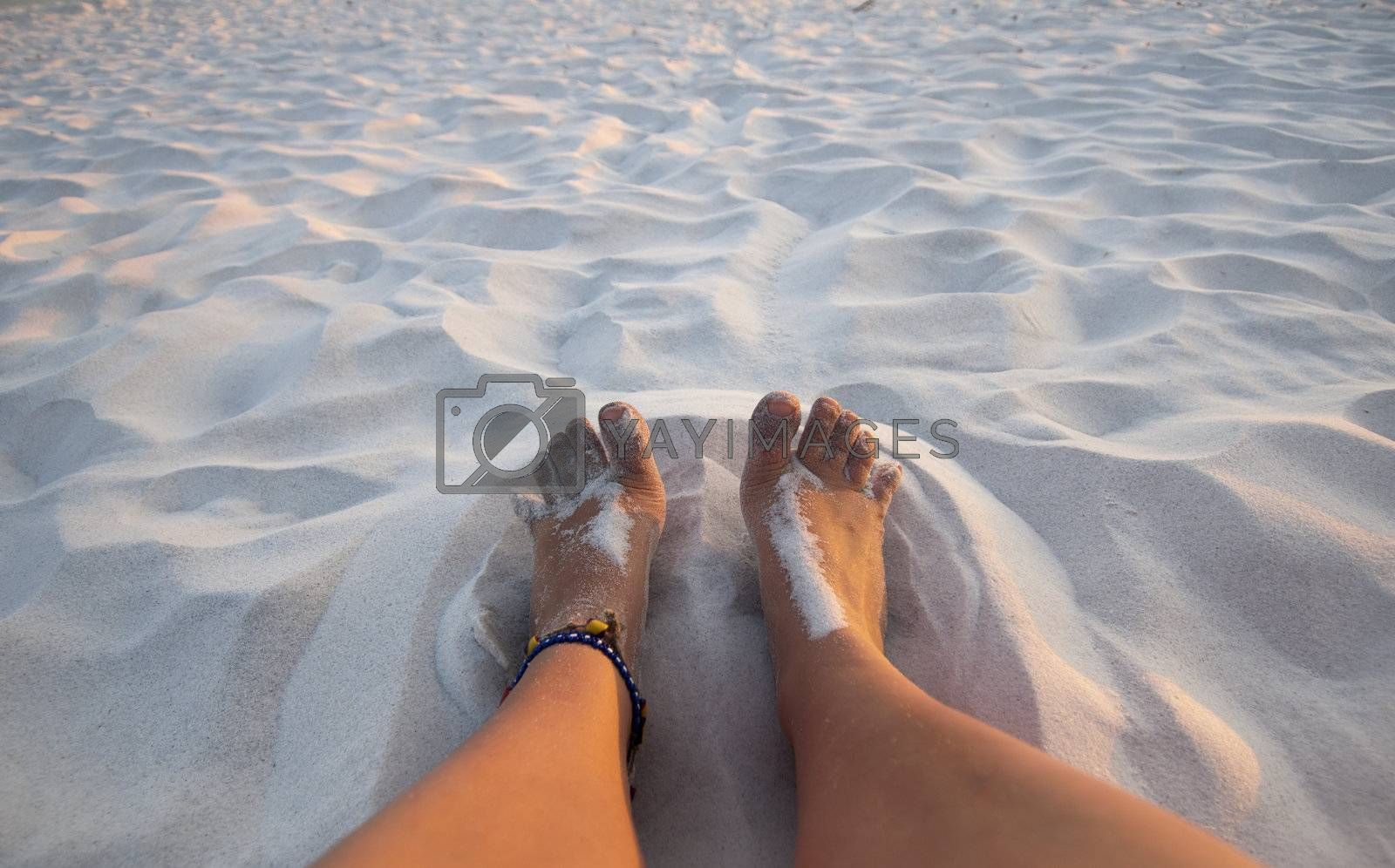 Feet playing in the sand on a white sand beach