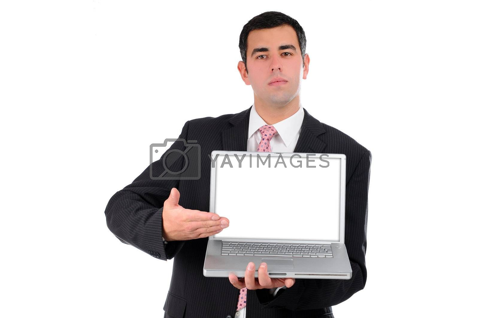 Portrait of a confident young businessman in a dark suit holding laptop and pointing his hand on screen isolated on white