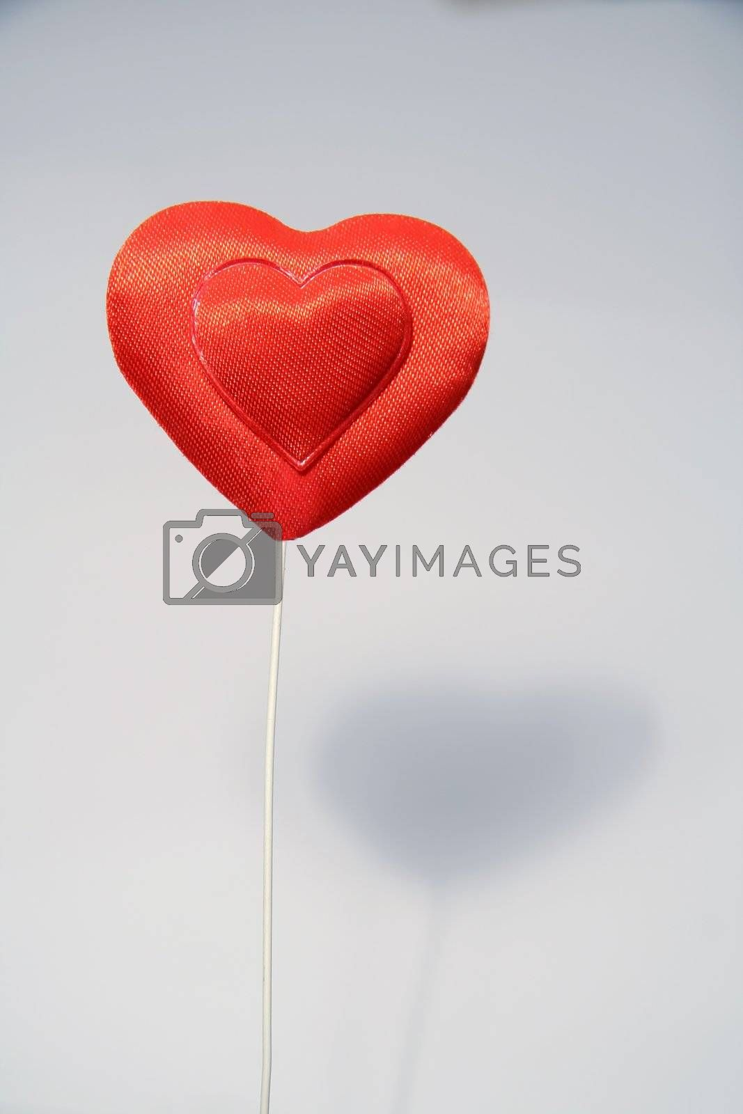 red heart on grey background, blurred shadow