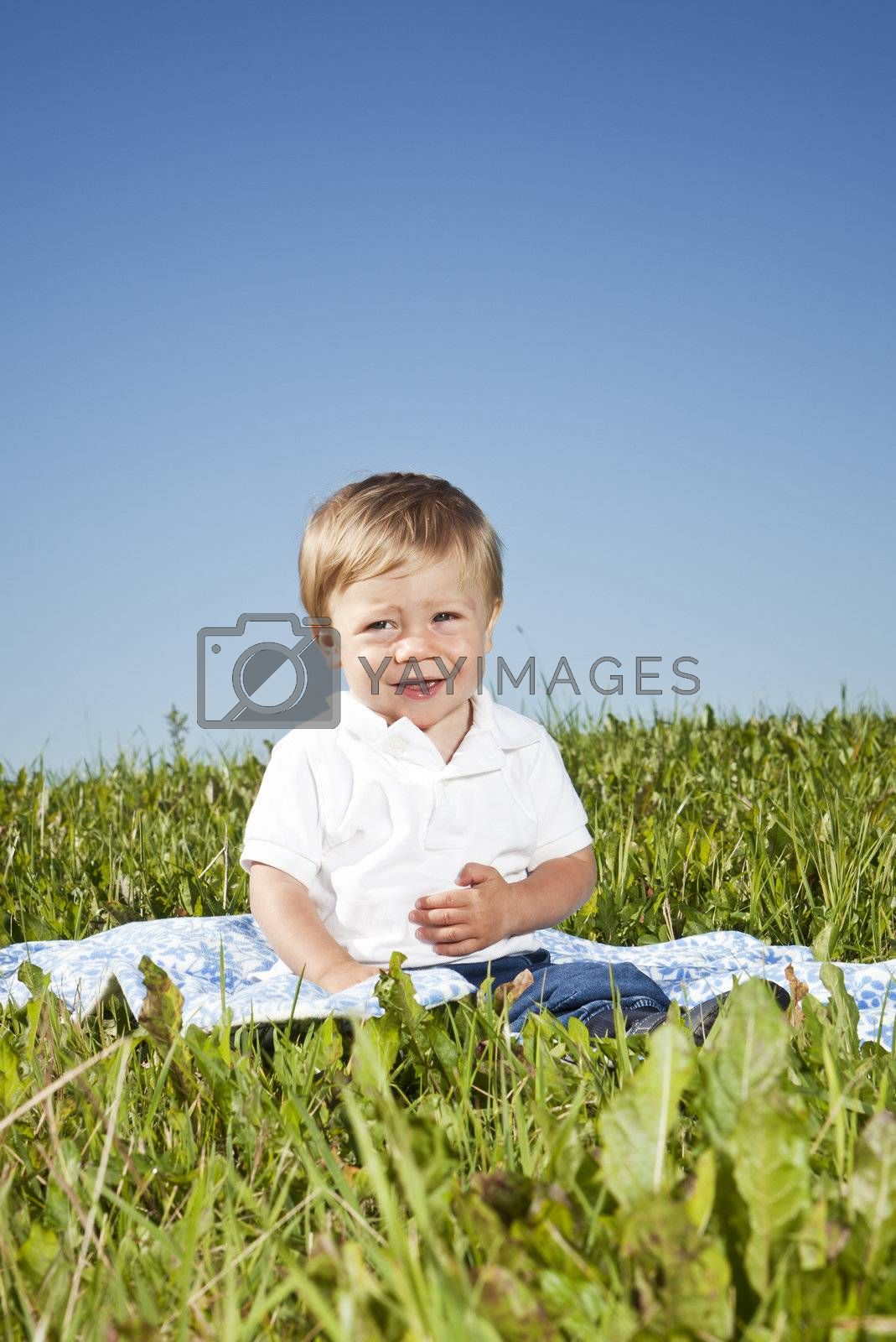 Child sitting in the grass on a sunny day