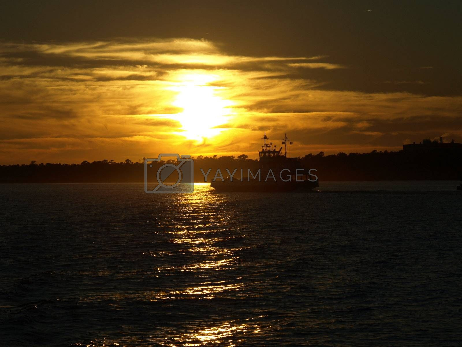 A ferry boat crosses the water against the setting sun