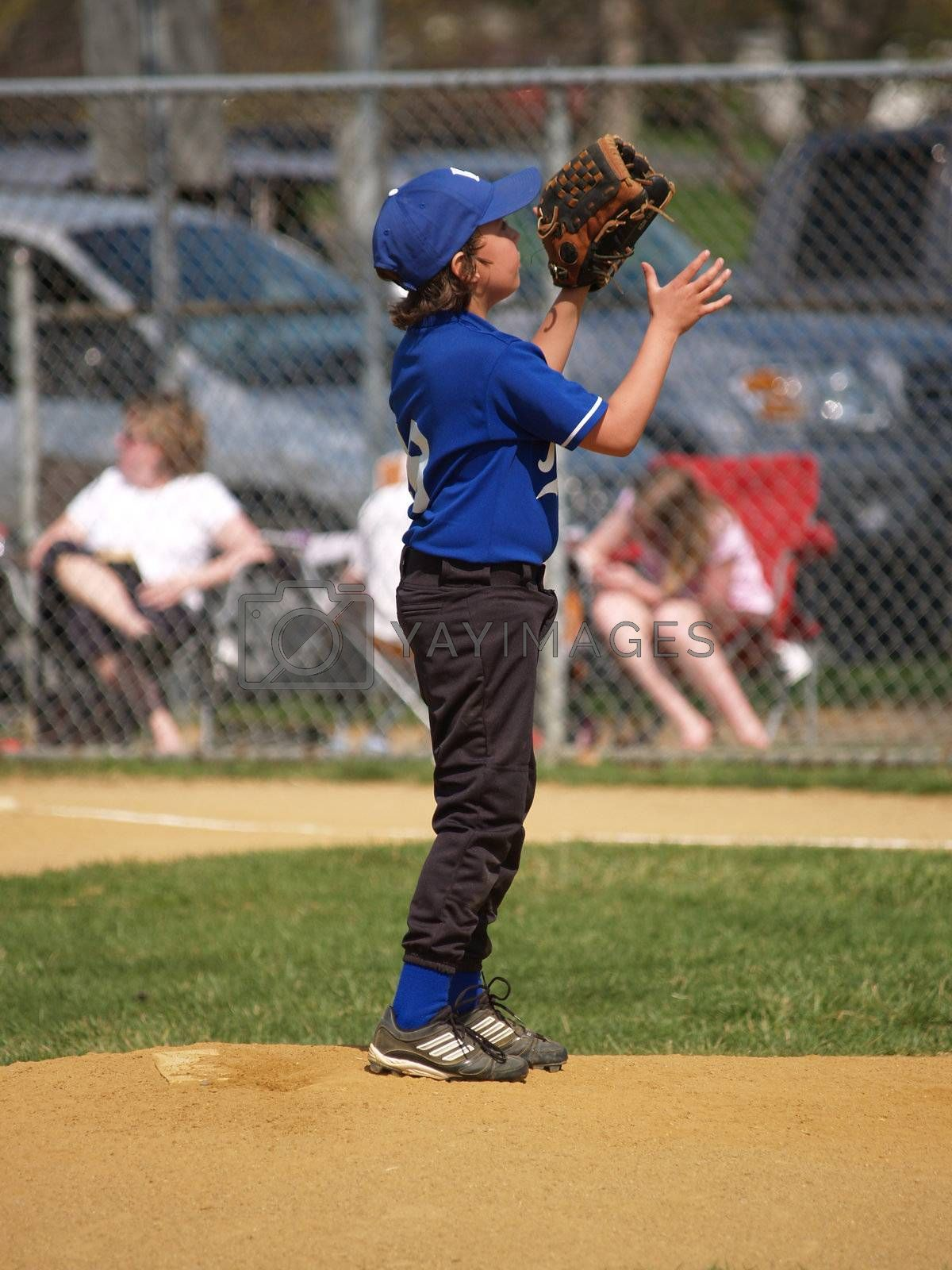 a little league baseball player waiting for the throw