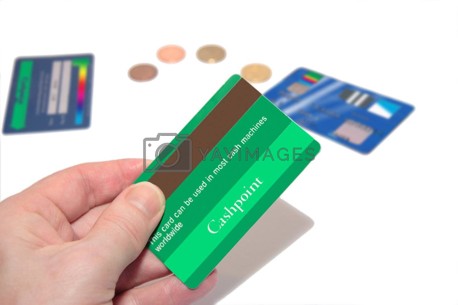a man holding a credit card (made up fake card ) with more fake cards and coins in the background
