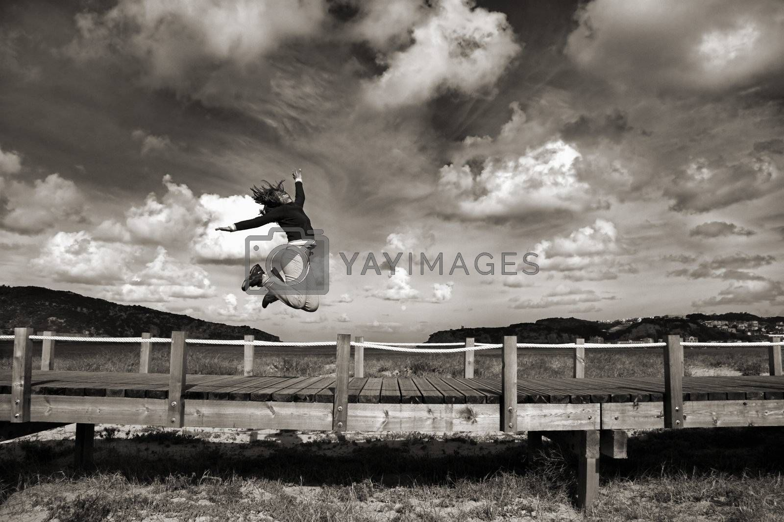 Young woman jumping for fun in a beautiful day (Black and white version)