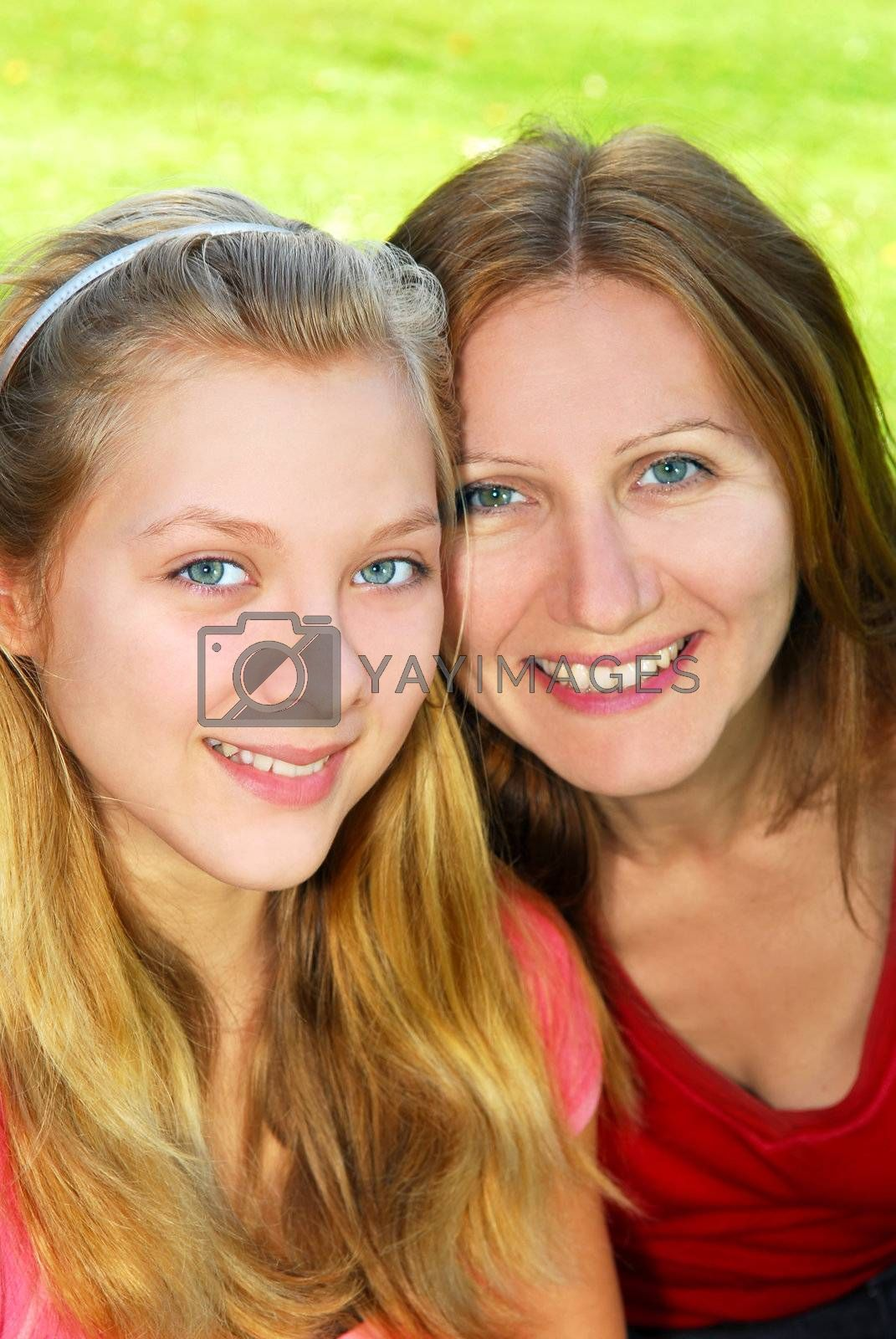 Portrait of smiling mother and daughter in summer park