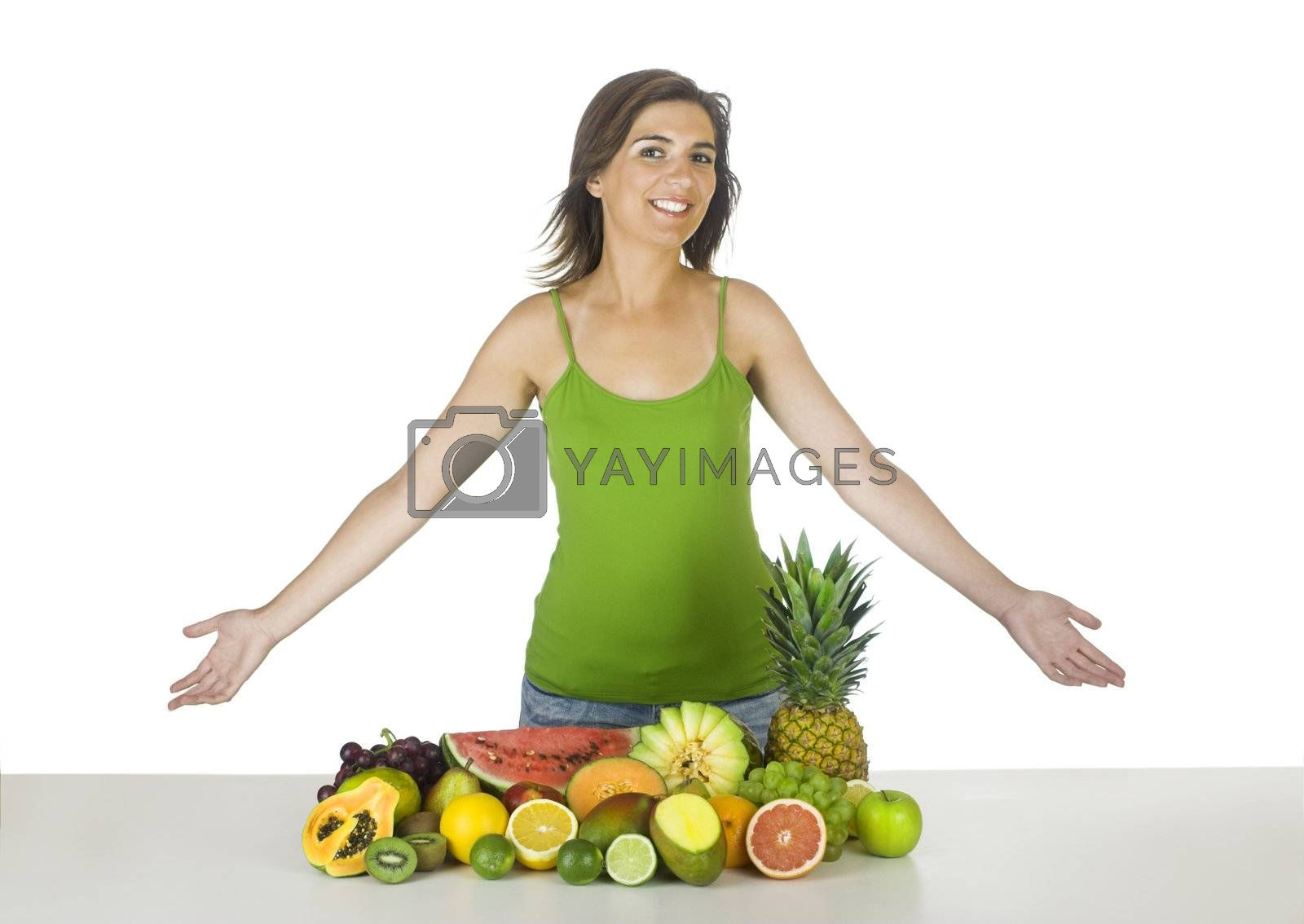 Beautiful and healthy woman with a lot of fruits in front of her