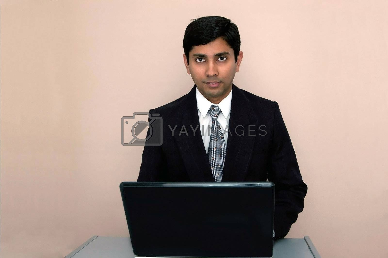 An handsome Indian businessman working on a laptop