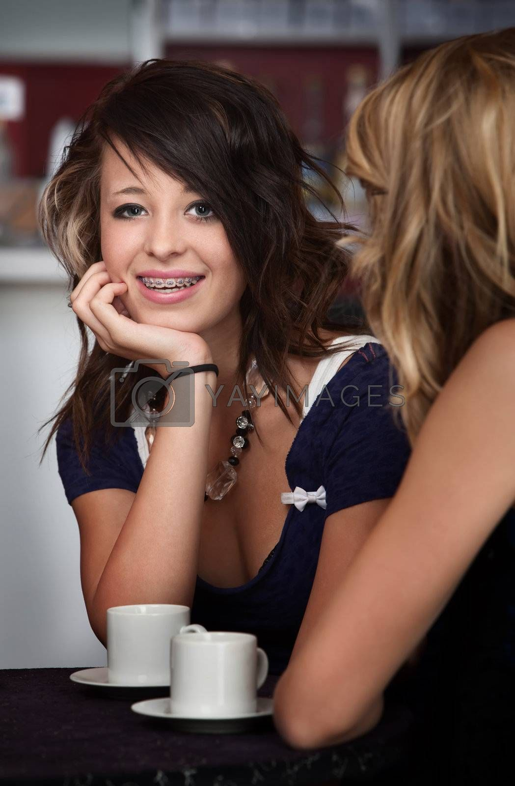 A cute teenaged girl with braces sitting at a table with a friend.
