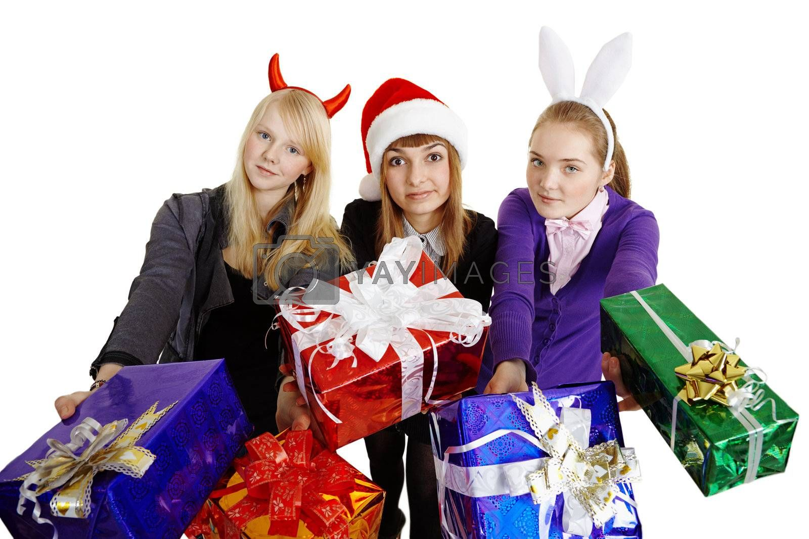 Three girls hand over New Year's gifts isolated on a white background