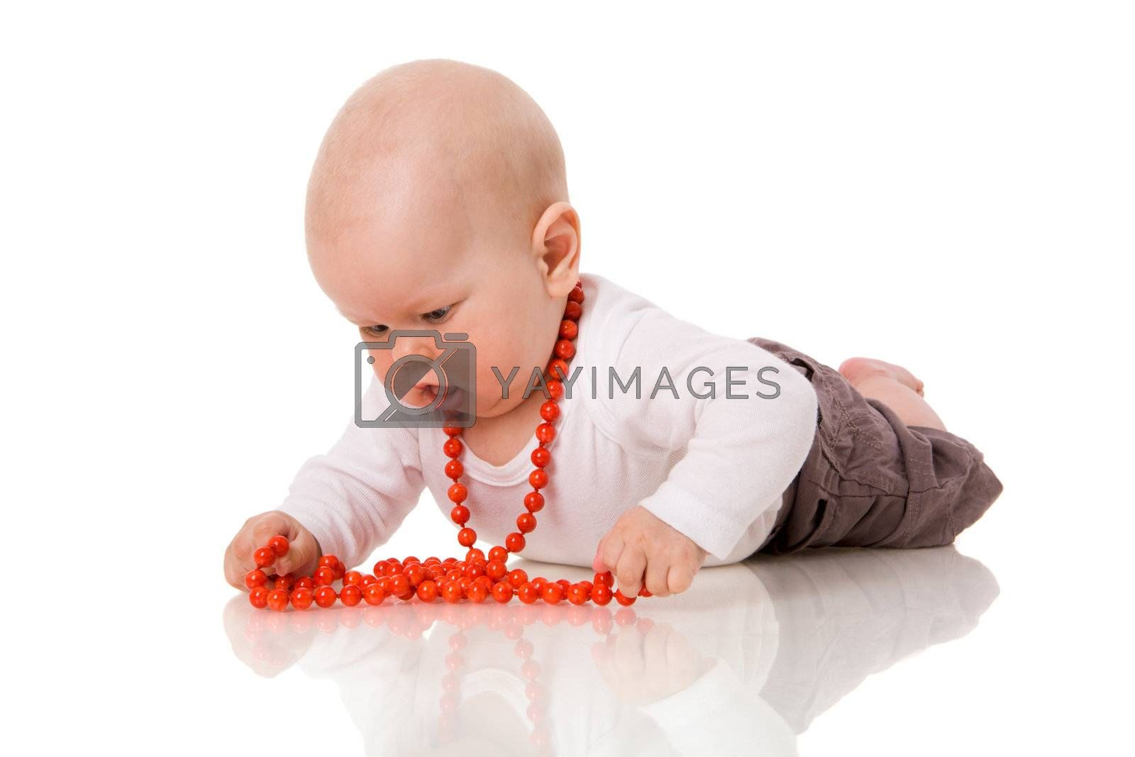 Baby lying on floor playing with beads isolated on white