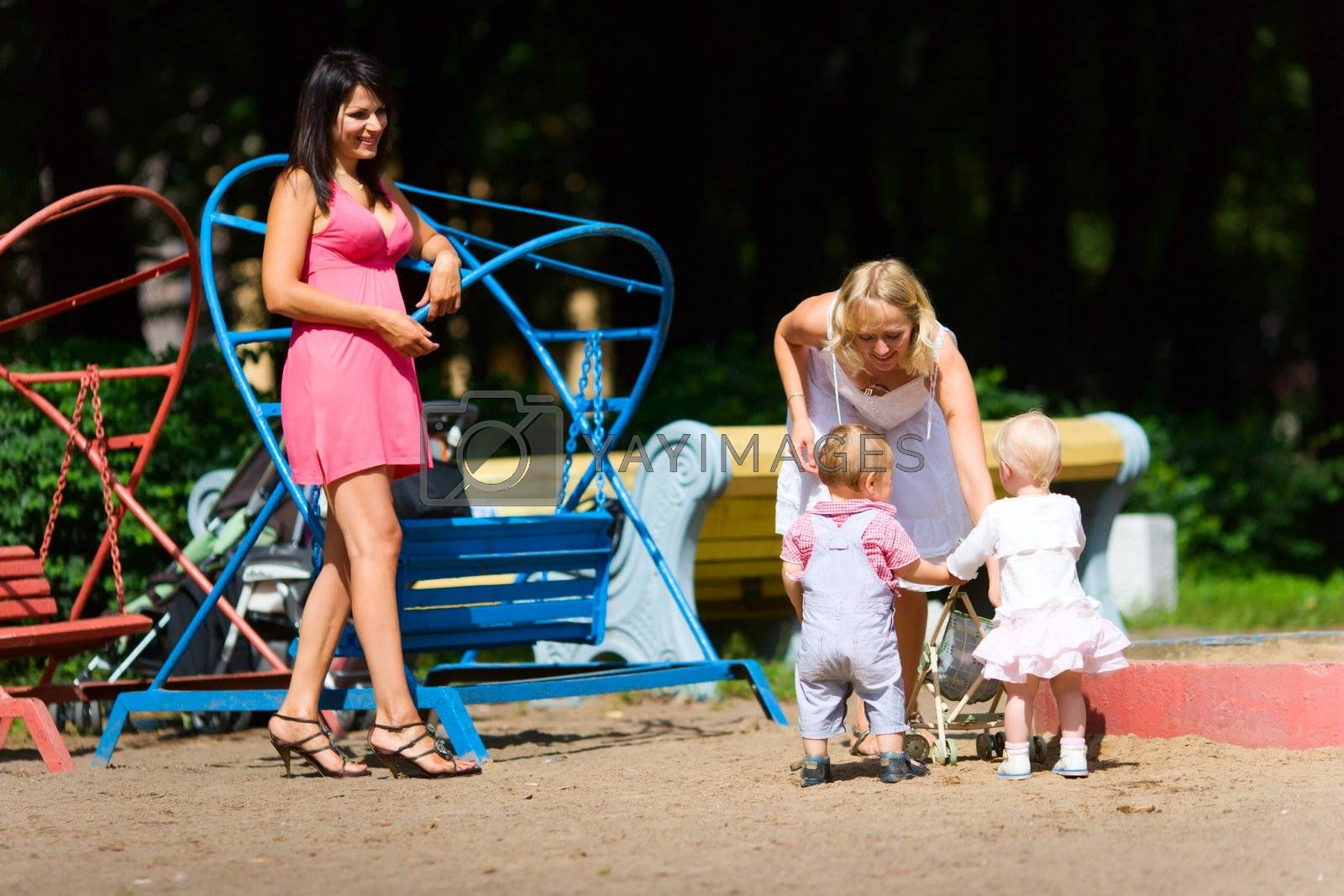 Two Mothers playing with children on city playground