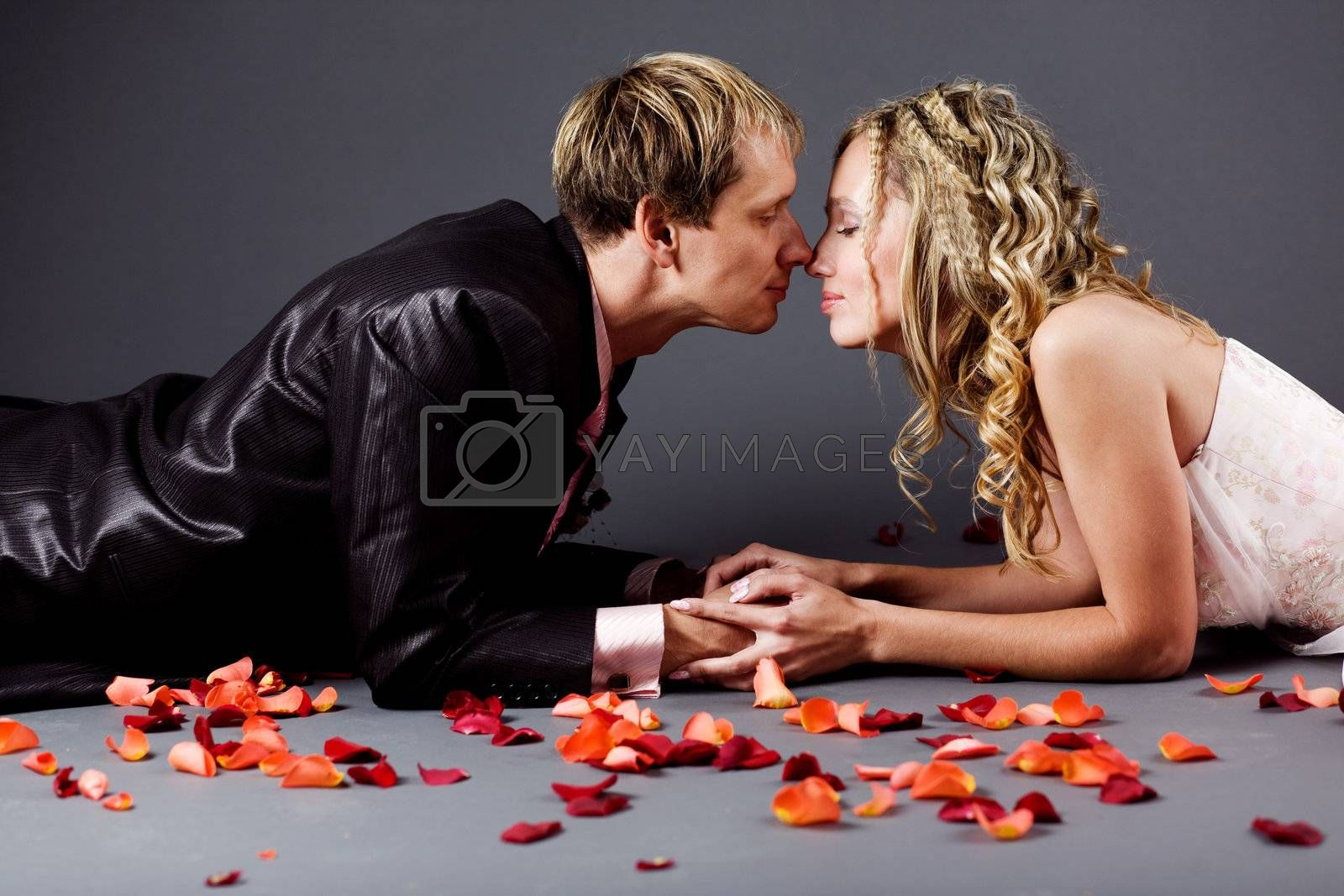 Kissing wedding couple lying among rose petals on gray studio background
