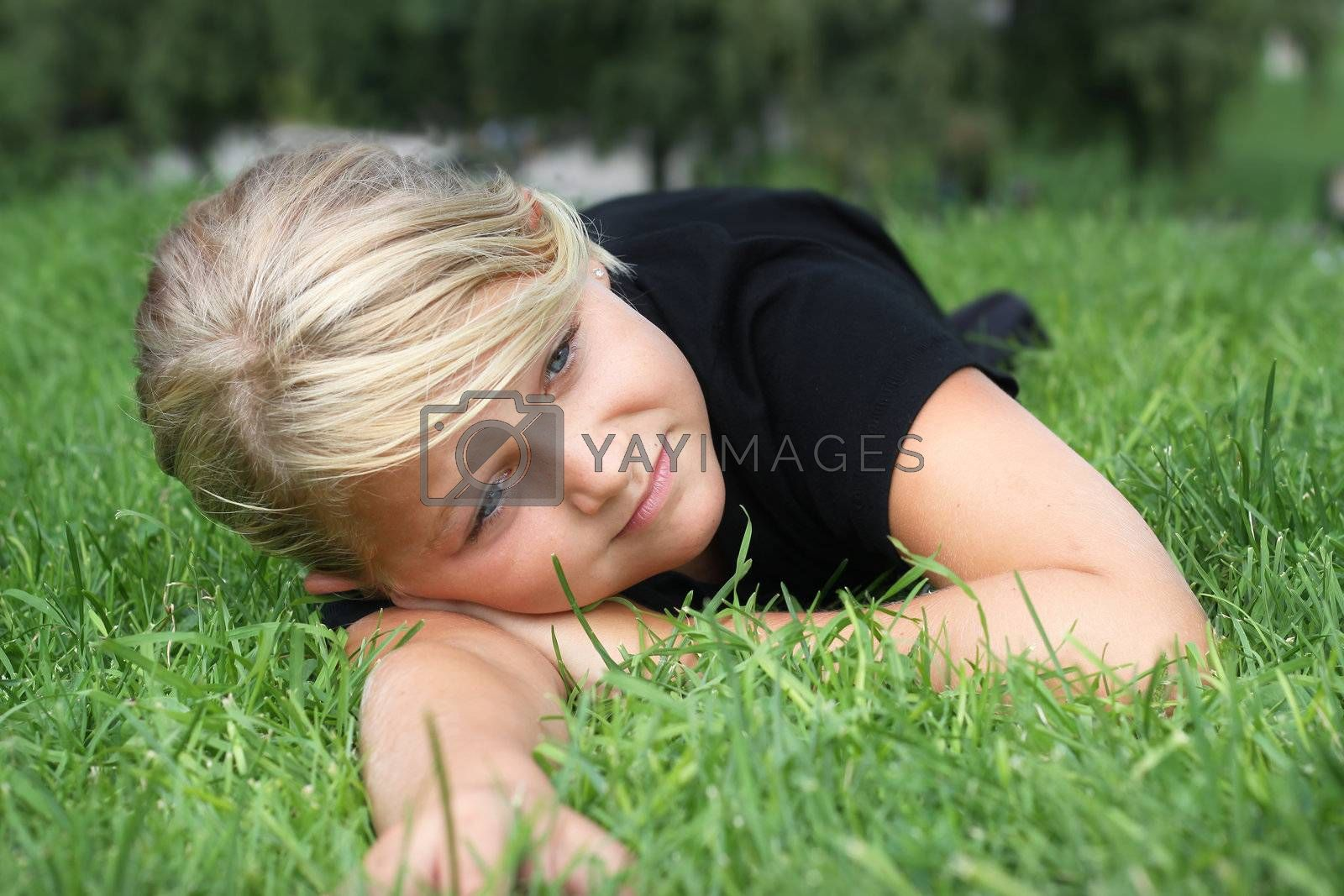 A young girl relaxing on green grass