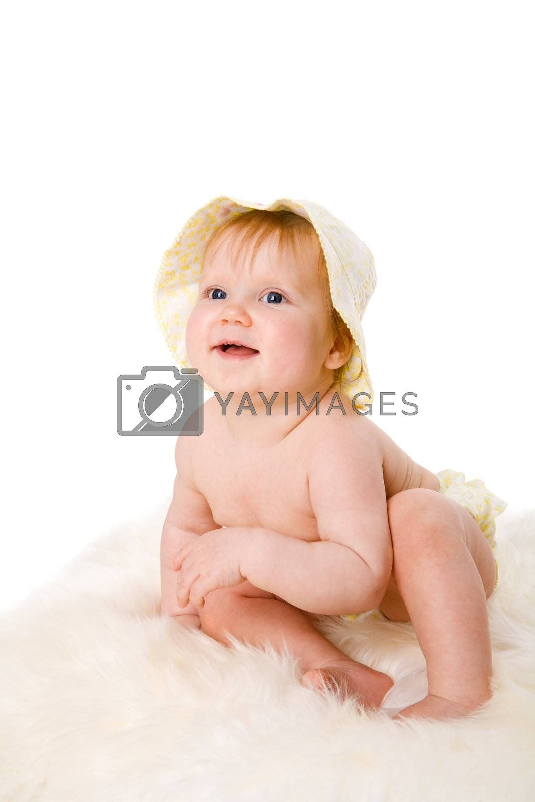 Baby sitting on fur floor wanna looking cheerful isolated
